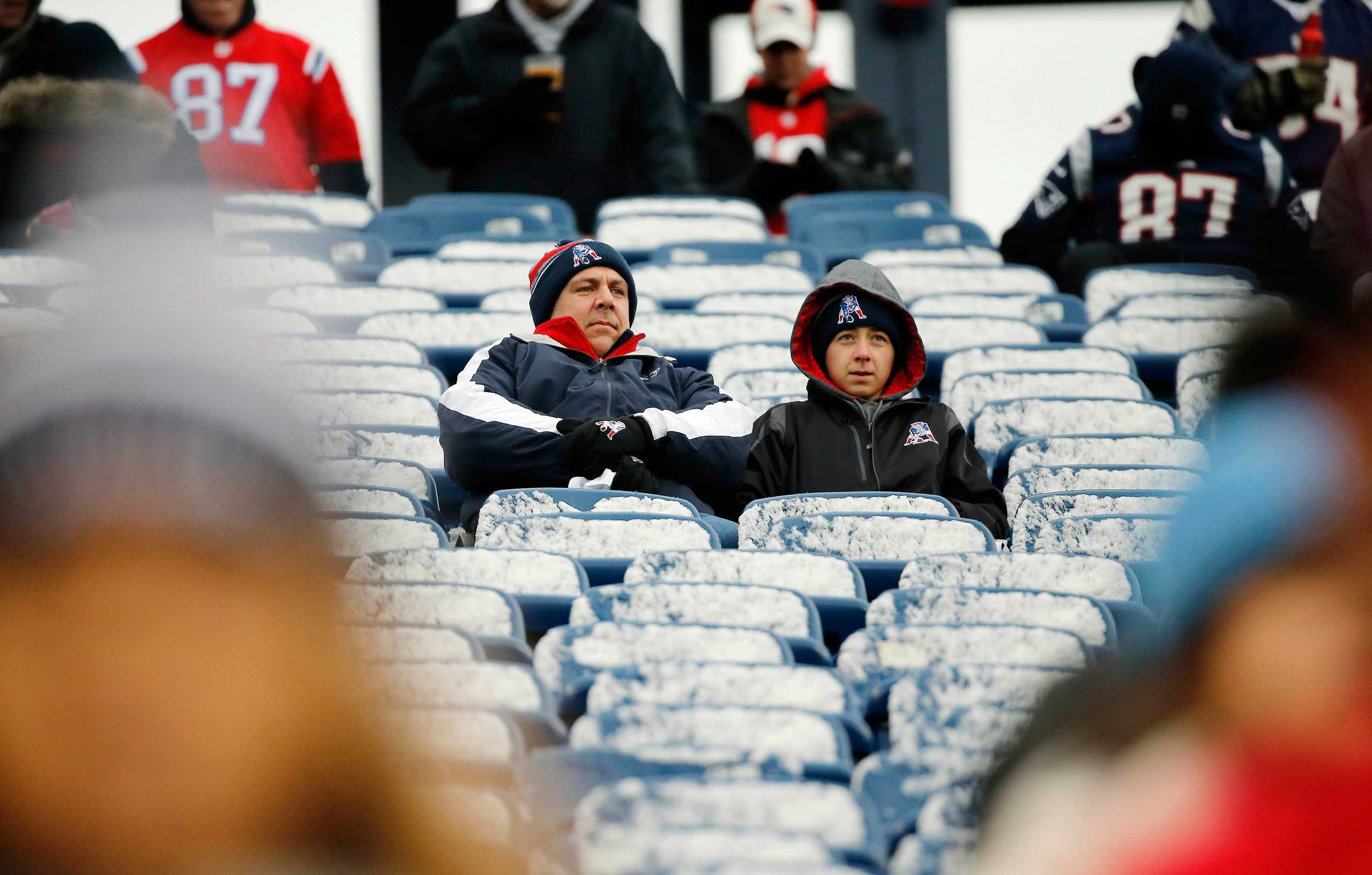 New England Patriots fans sit in seats coated by a light morning snow before an NFL football game between the Patriots and the Denver Broncos on Nov. 2, 2014, at Gillette Stadium in Foxborough, Mass.