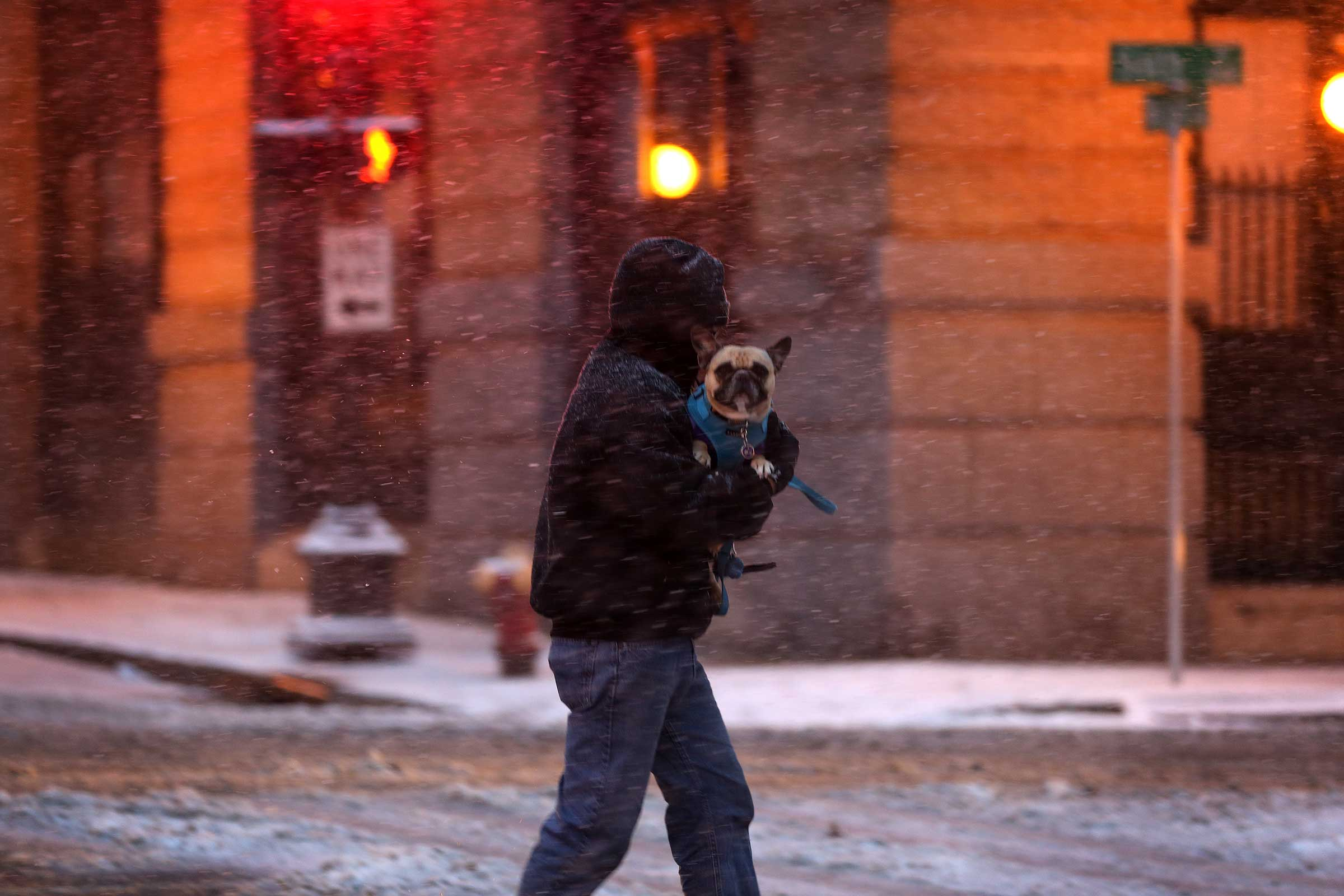 A man holds his dog as he rushes across the street in downtown St. Paul, Minn., during the first snowstorm of the season on, Nov. 10, 2014.