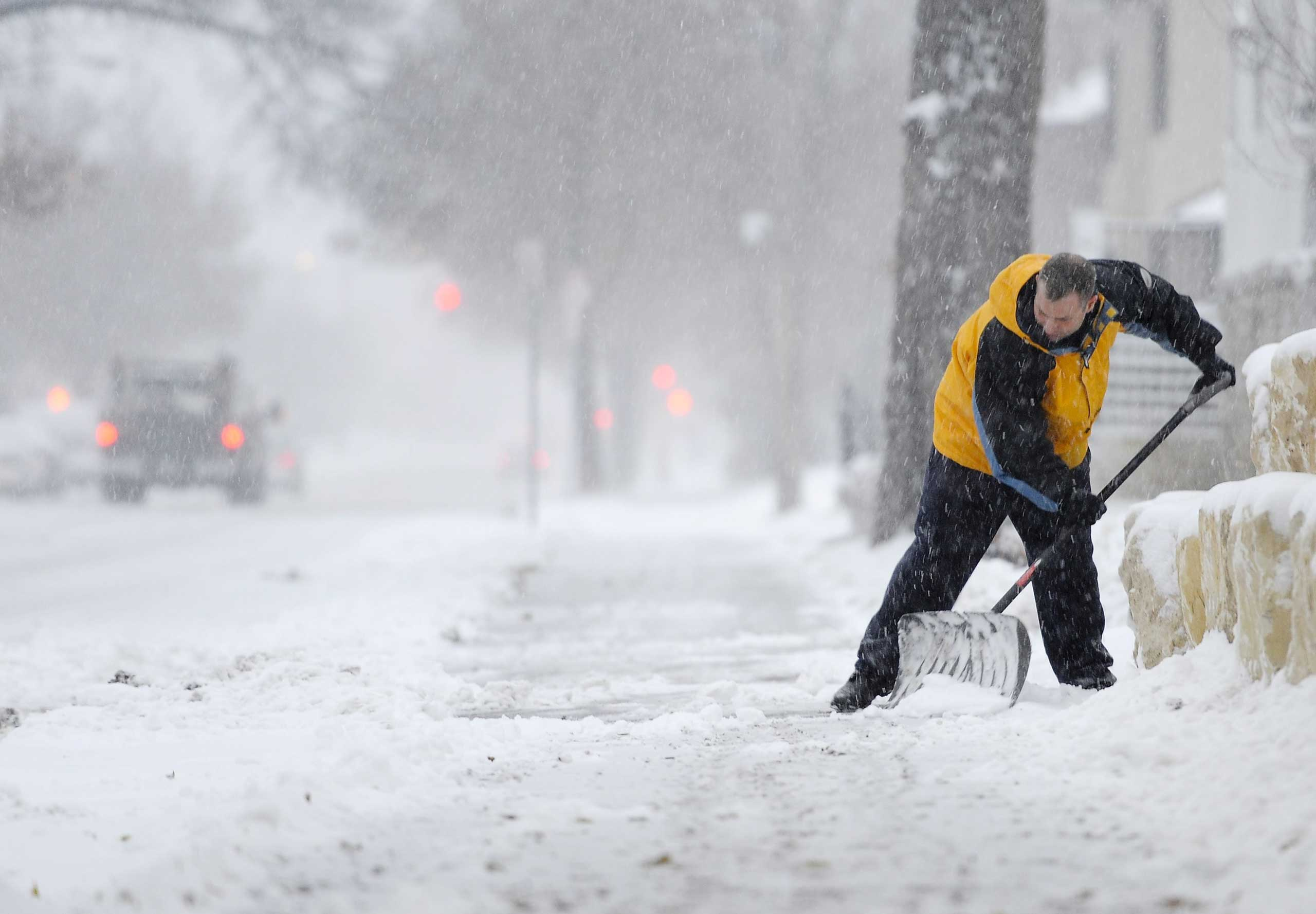 Mike Schultz of Minneapolis clears a sidewalk as he tries to keep up with the snow during the season's first snowstorm in Minneapolis, on Nov. 10, 2014.