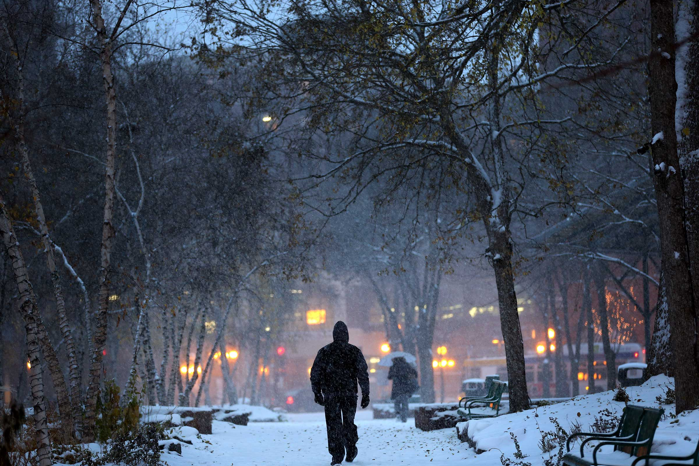 A man walks through Mears Park in downtown St. Paul, Minn., during the first snowstorm of the season on Nov. 10, 2014.
