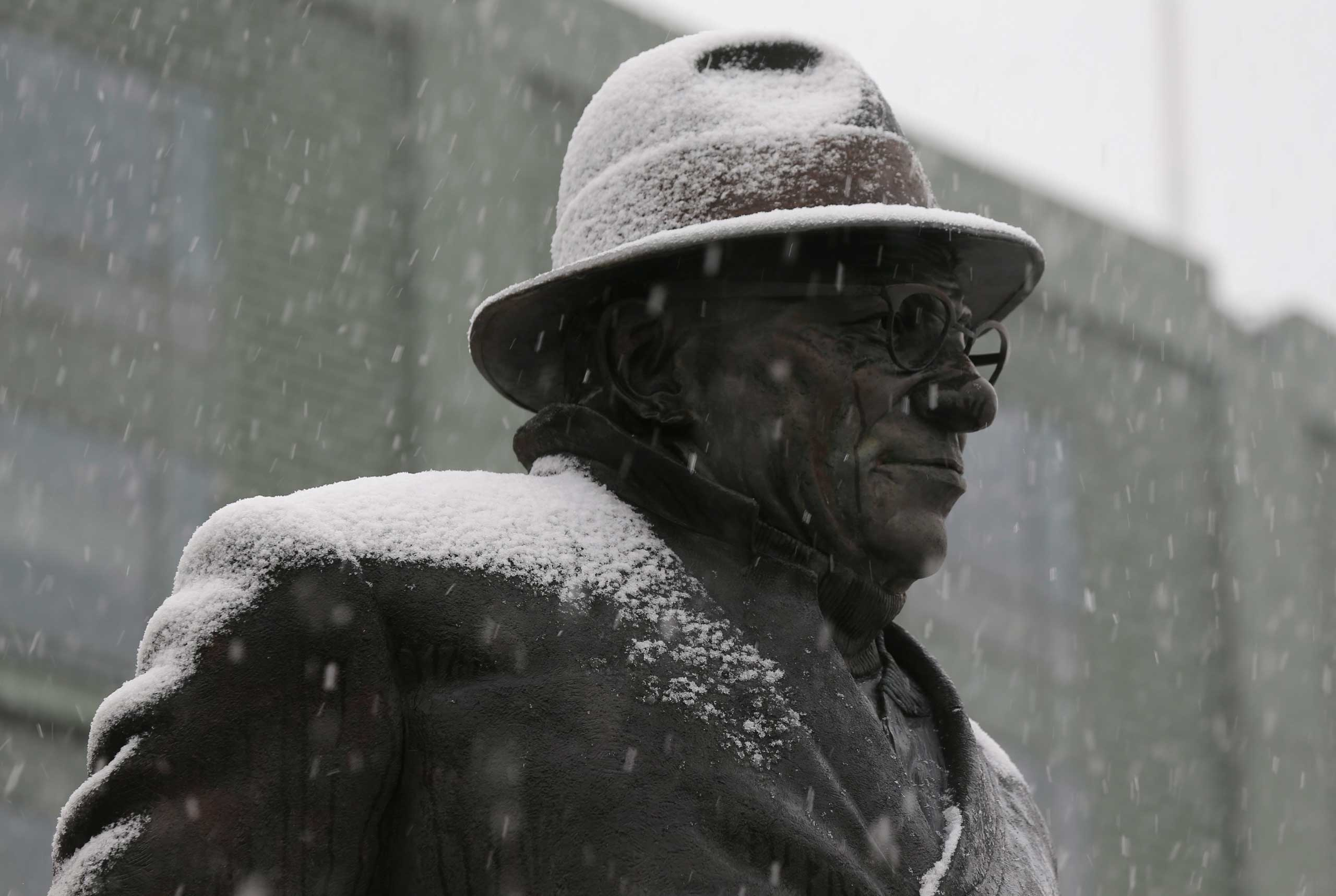 Snow falls on the Vince Lombardi statue at Lambeau Field in Green Bay, Wis. on Nov. 10, 2014.