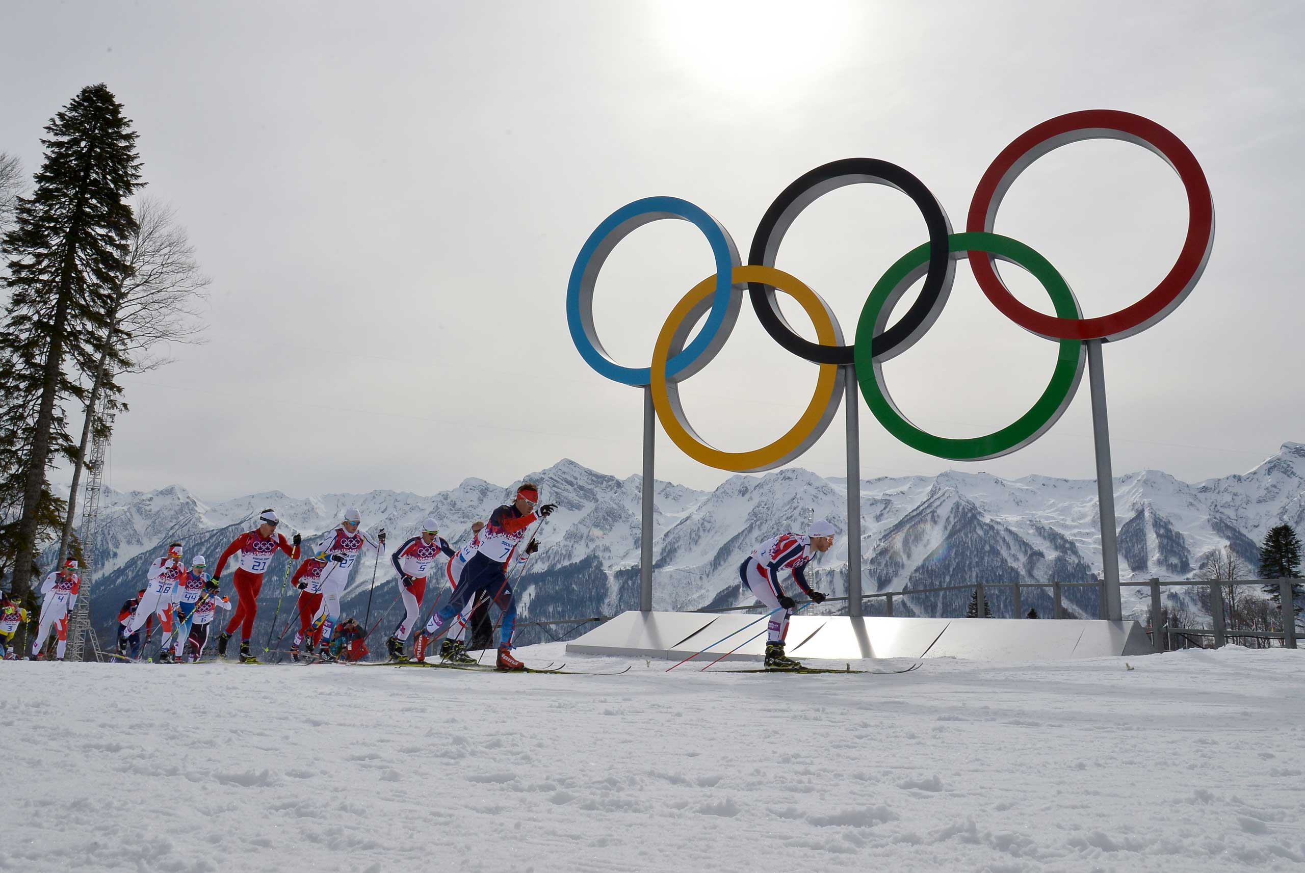 Skiers compete past the Olympic Rings in the Men's Cross-Country Skiing 15km + 15km Skiathlon at the Laura Cross-Country Ski and Biathlon Center during the Sochi Winter Olympics in Russia on Feb. 9, 2014.