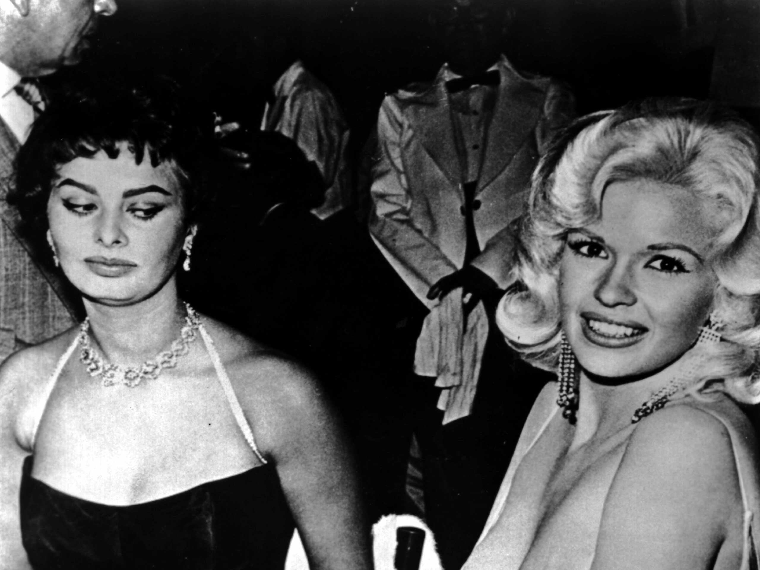 Jayne Mansfield tries to steal the show in a very low cut dress at a party thrown by 20th Century-Fox for Sophia Loren on April 12, 1957 in Los Angeles.
