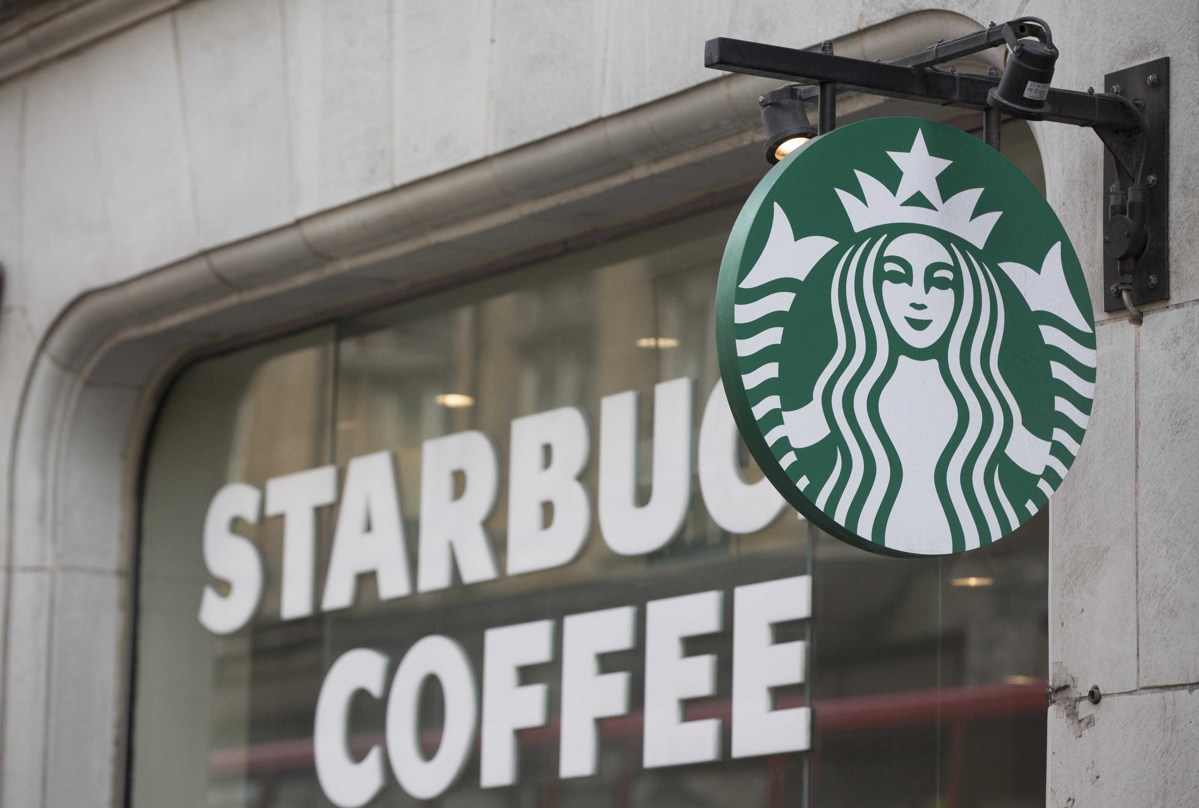 The Starbucks Corp. logo hangs outside of a coffee shop in London, U.K., on Monday, June 9, 2014.