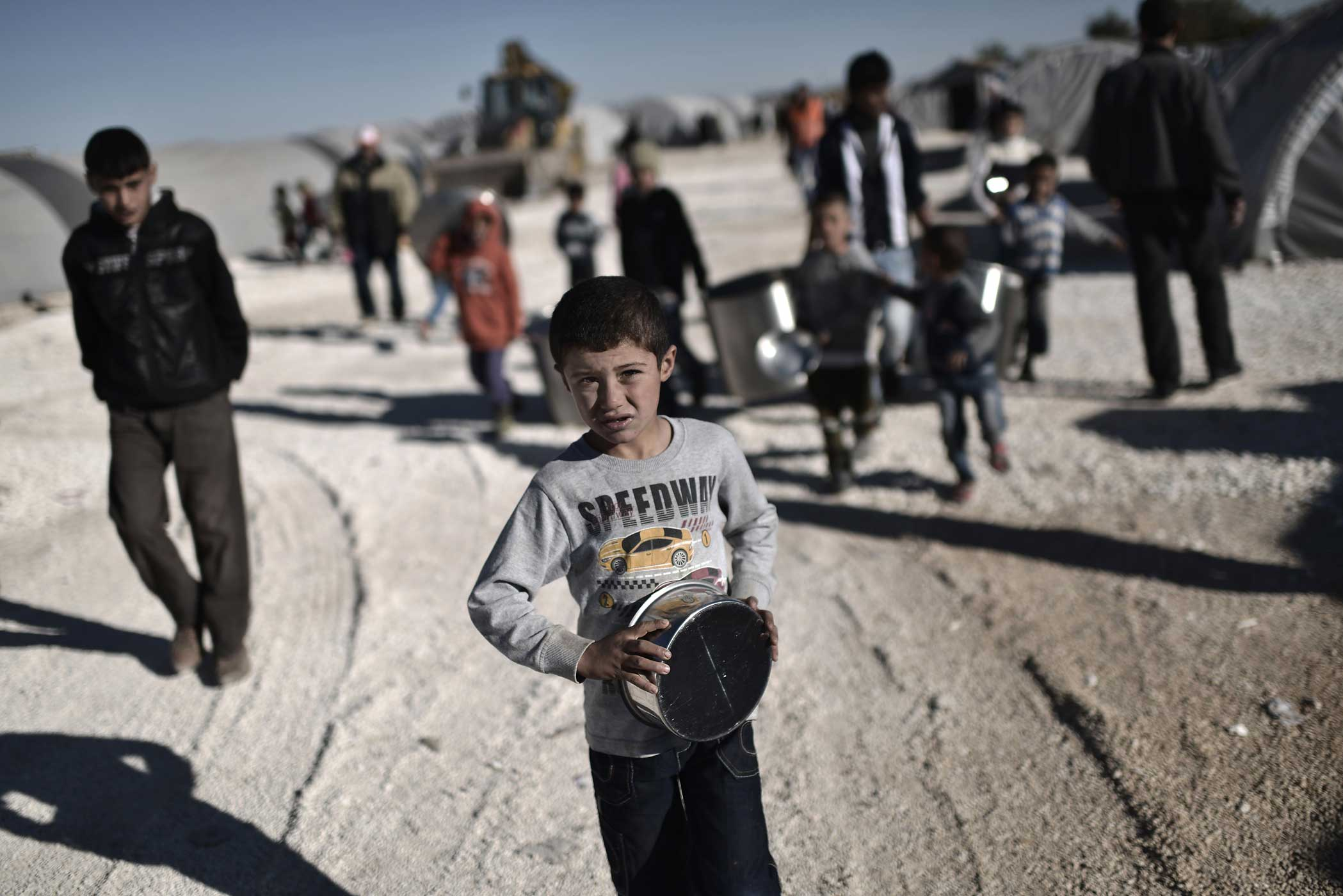 A Syrian Kurdish boy looks on as he stands in a refugee camp in the town of Suruc, Turkey, on November 5, 2014.