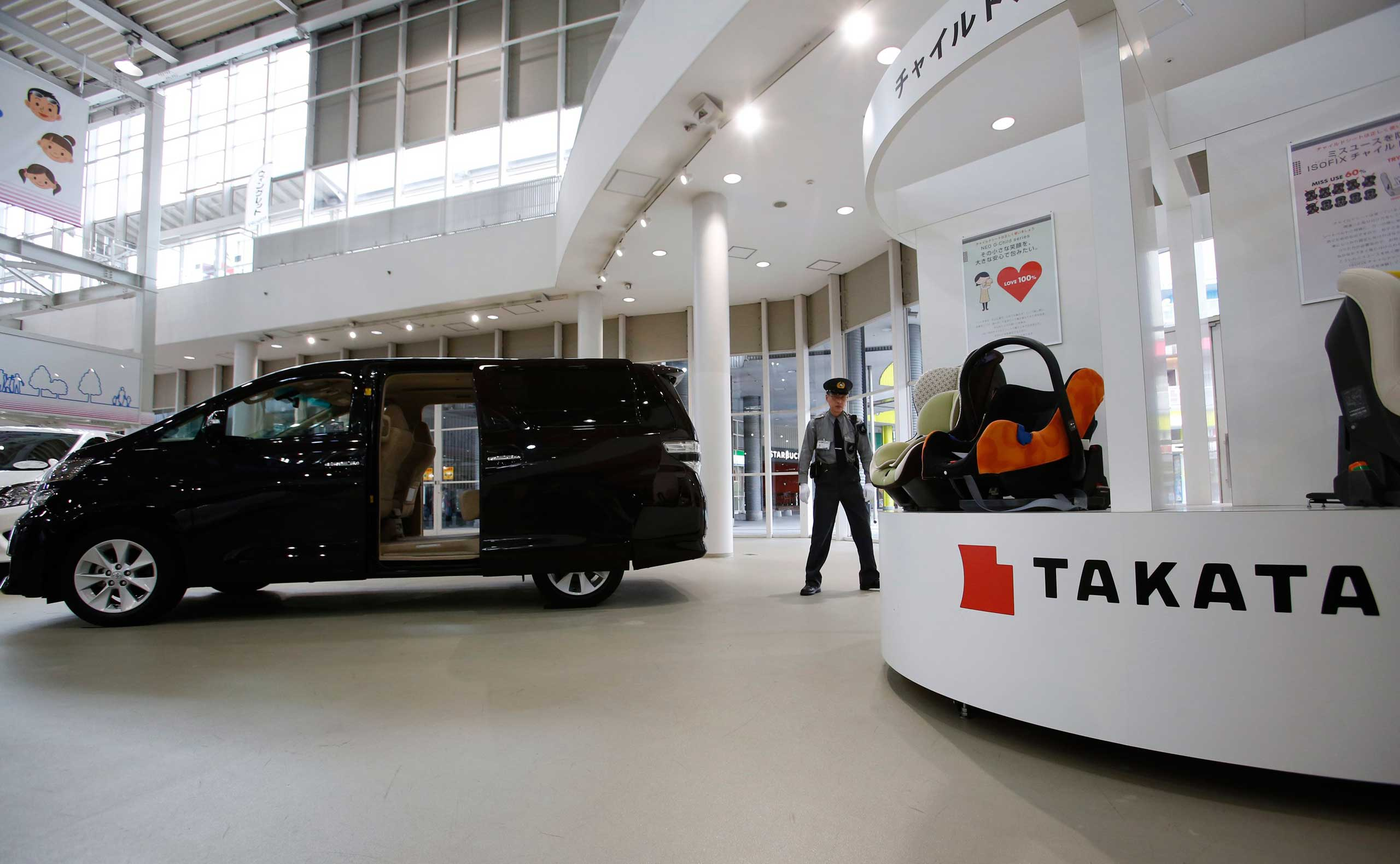 A security guard stands by child seats, manufactured and displayed by Takata Corp. at a Toyota showroom in Tokyo, Nov. 6, 2014.