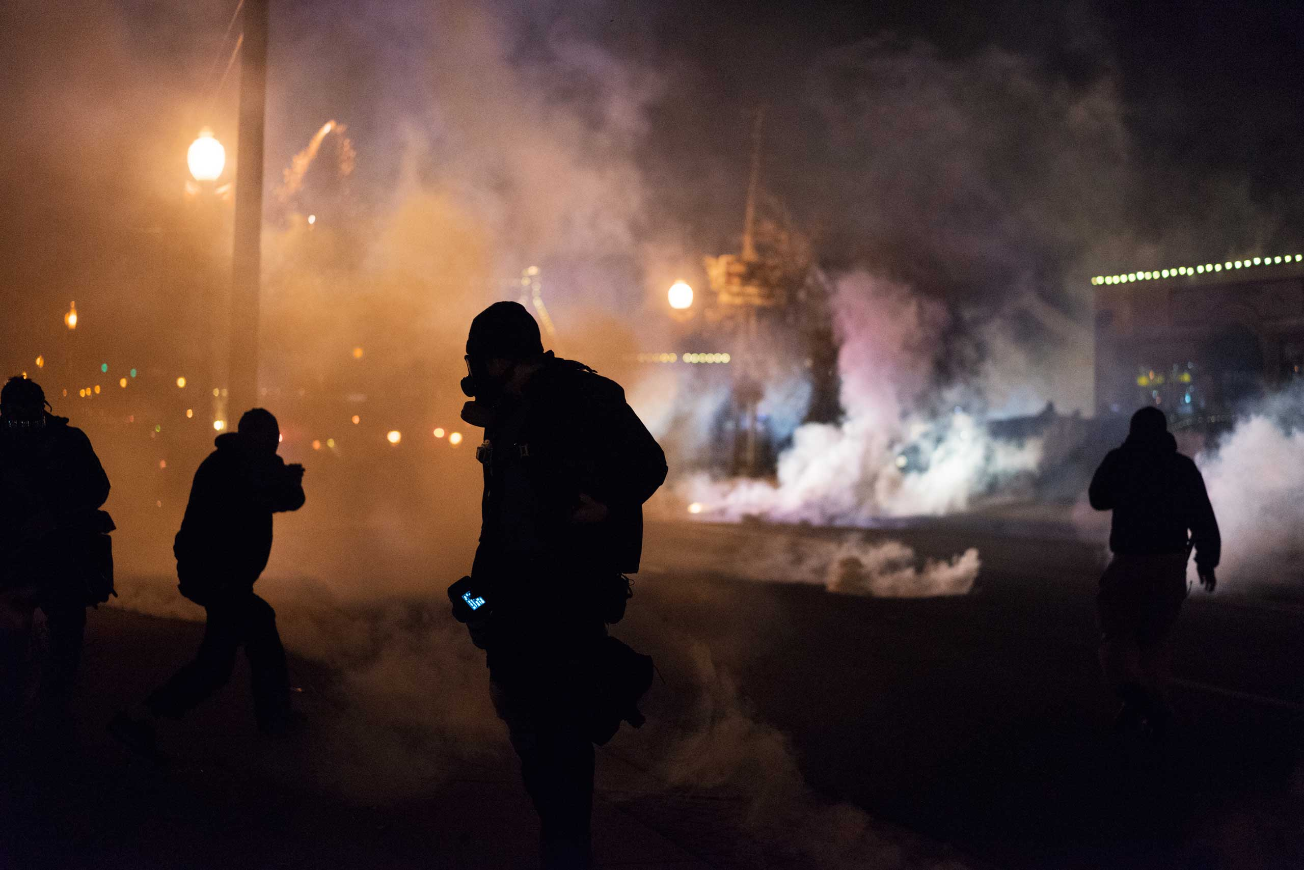 Protesters stand amid tear gas and smoke in Ferguson, Mo. on Nov. 24, 2014.