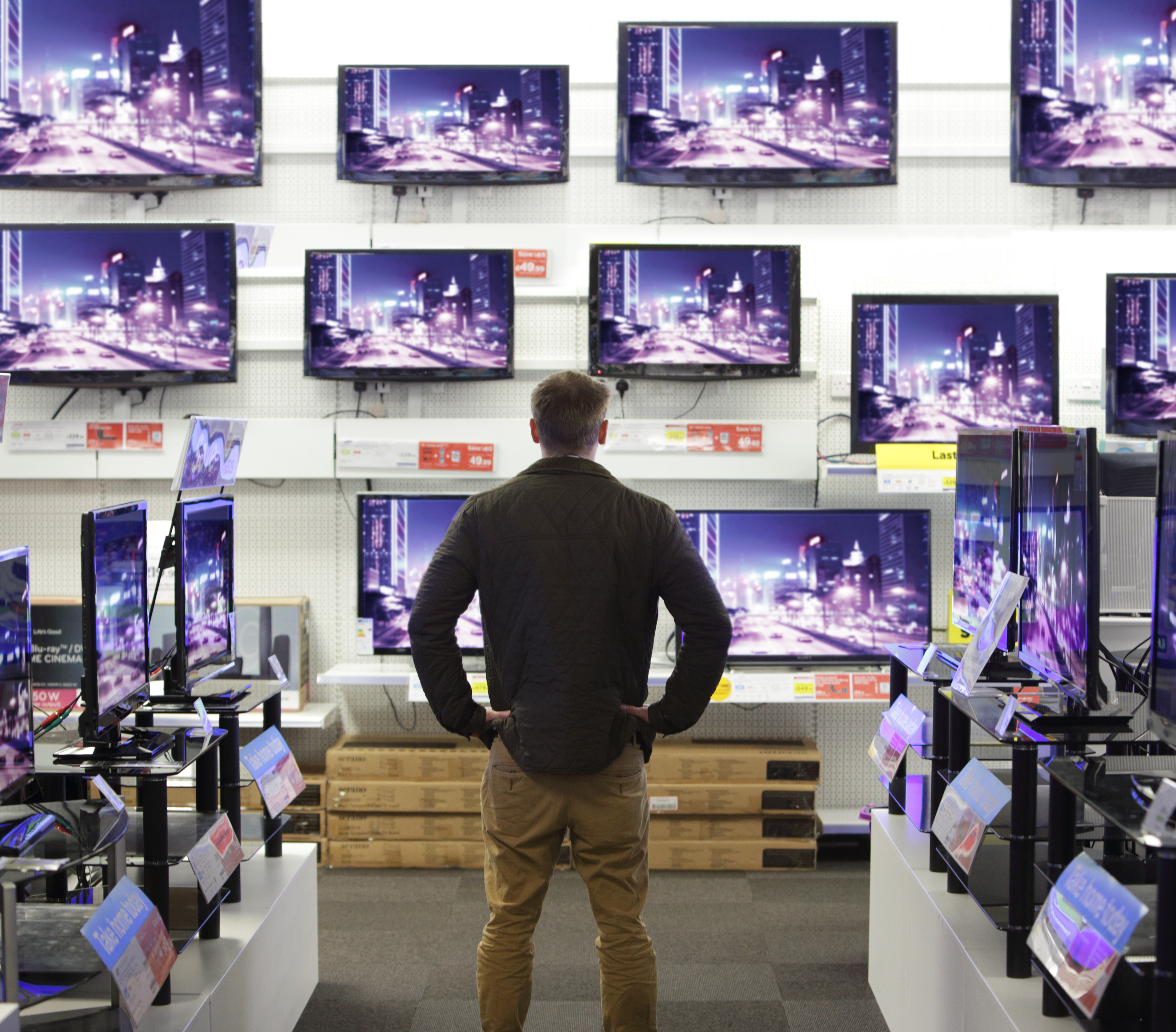 Man standing in shop surrounded by televisions