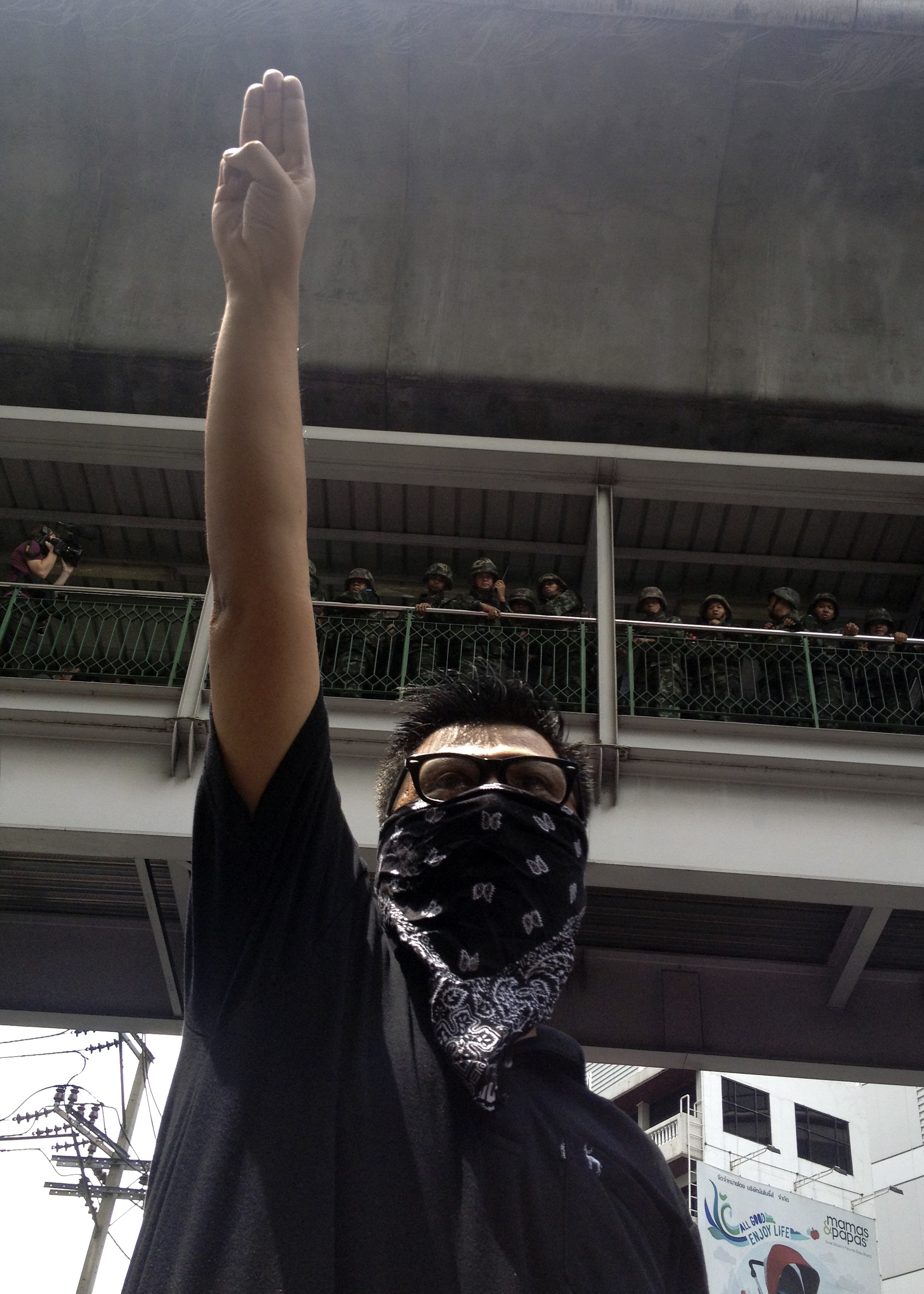 An anticoup protester gives a three-finger salute as soldiers keep eyes on him from an elevated walkway near a rally site in central Bangkok on June 1, 2014