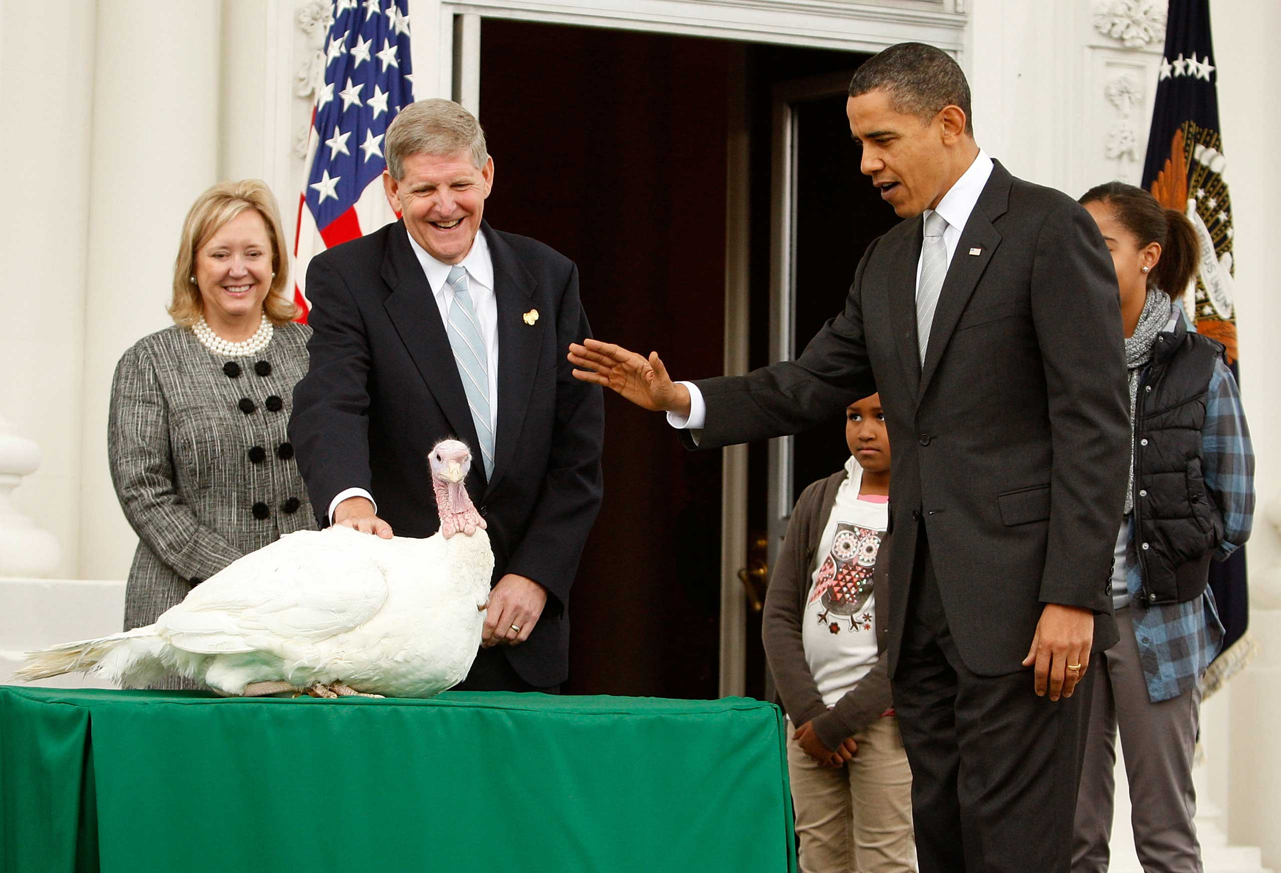 "President Barack Obama pardons a turkey named ""Courage"" as daughter Sasha looks on during an event to pardon the turkey at the White House on Nov. 25, 2009 in Washington, D.C."