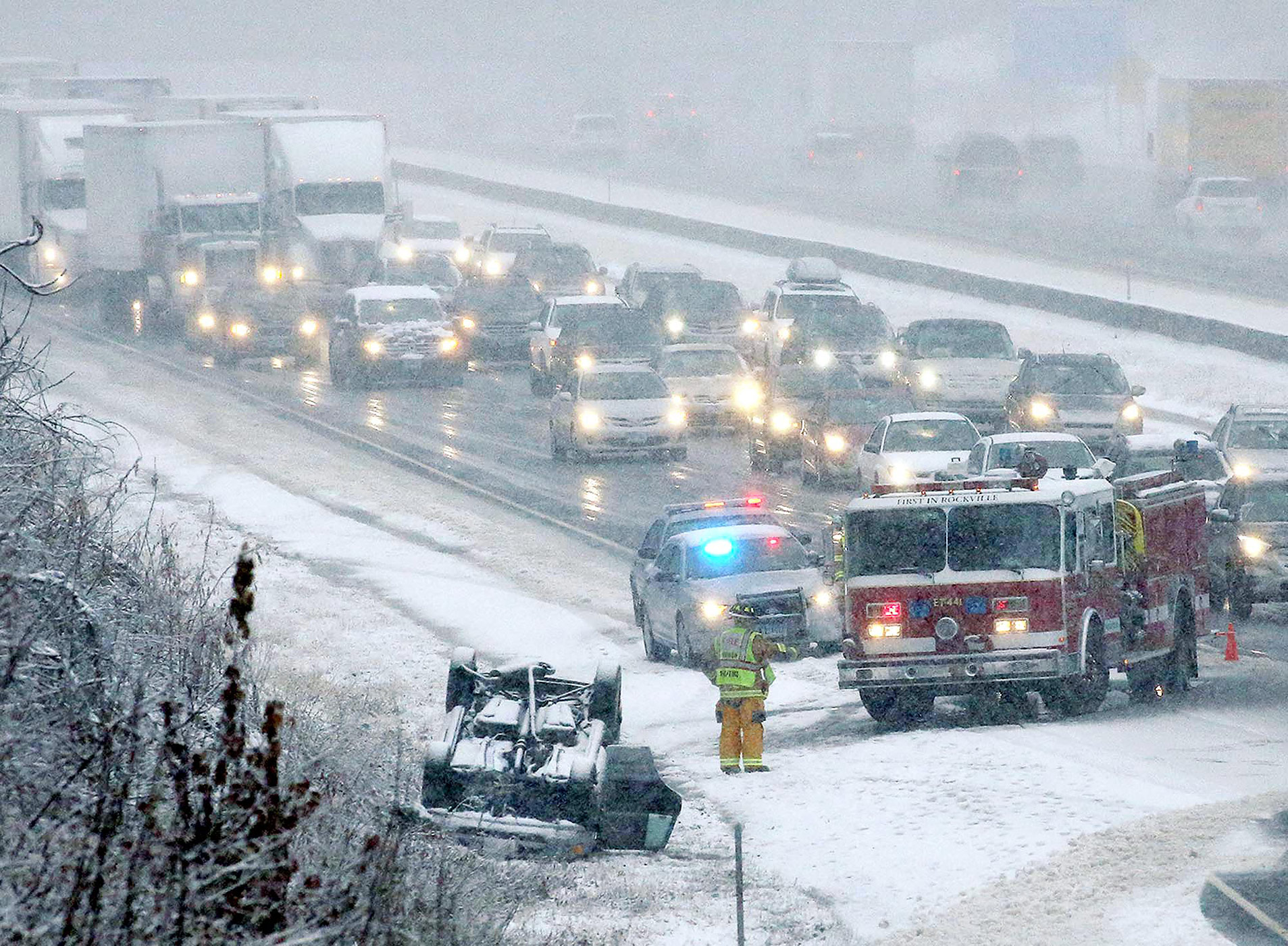 An over-turned automobile on Interstate 84 snarls traffic, Wednesday, Nov. 26, 2014 in Vernon, Conn.