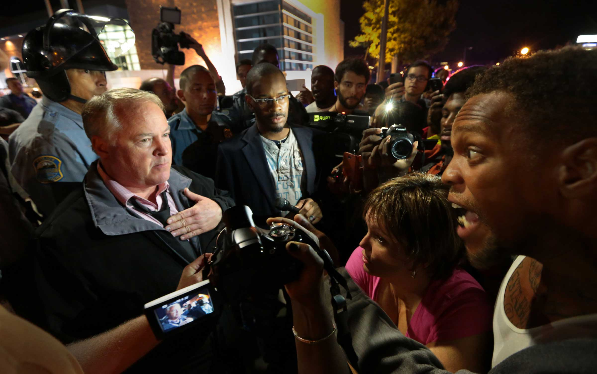 Ferguson Police Chief Tom Jackson, left, addresses protesters in front of the Ferguson Police Department, on Sept. 25, 2014. Protesters have called for Jackson to resign.
