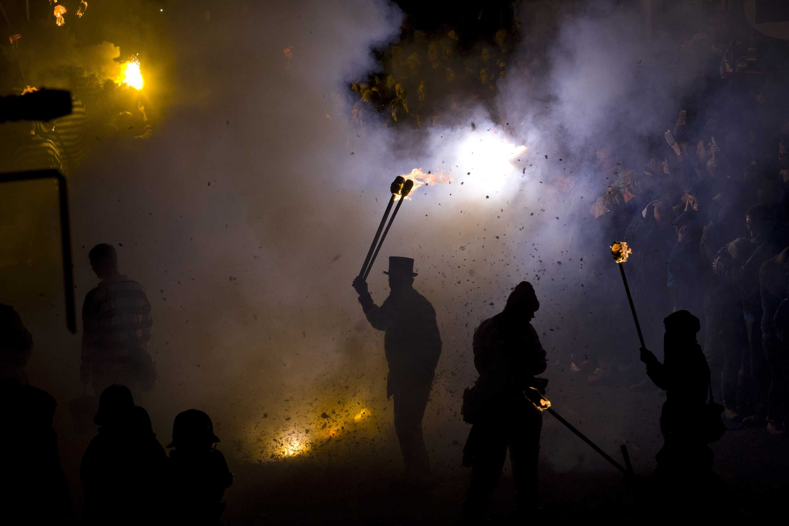 Nov. 5, 2014. A participant in costume holds aloft a torch as bonfire societies parade through the streets of Lewes in Sussex in the U.K., during the traditional Bonfire Night, commemorating the memory of the seventeen Protestant martyrs.