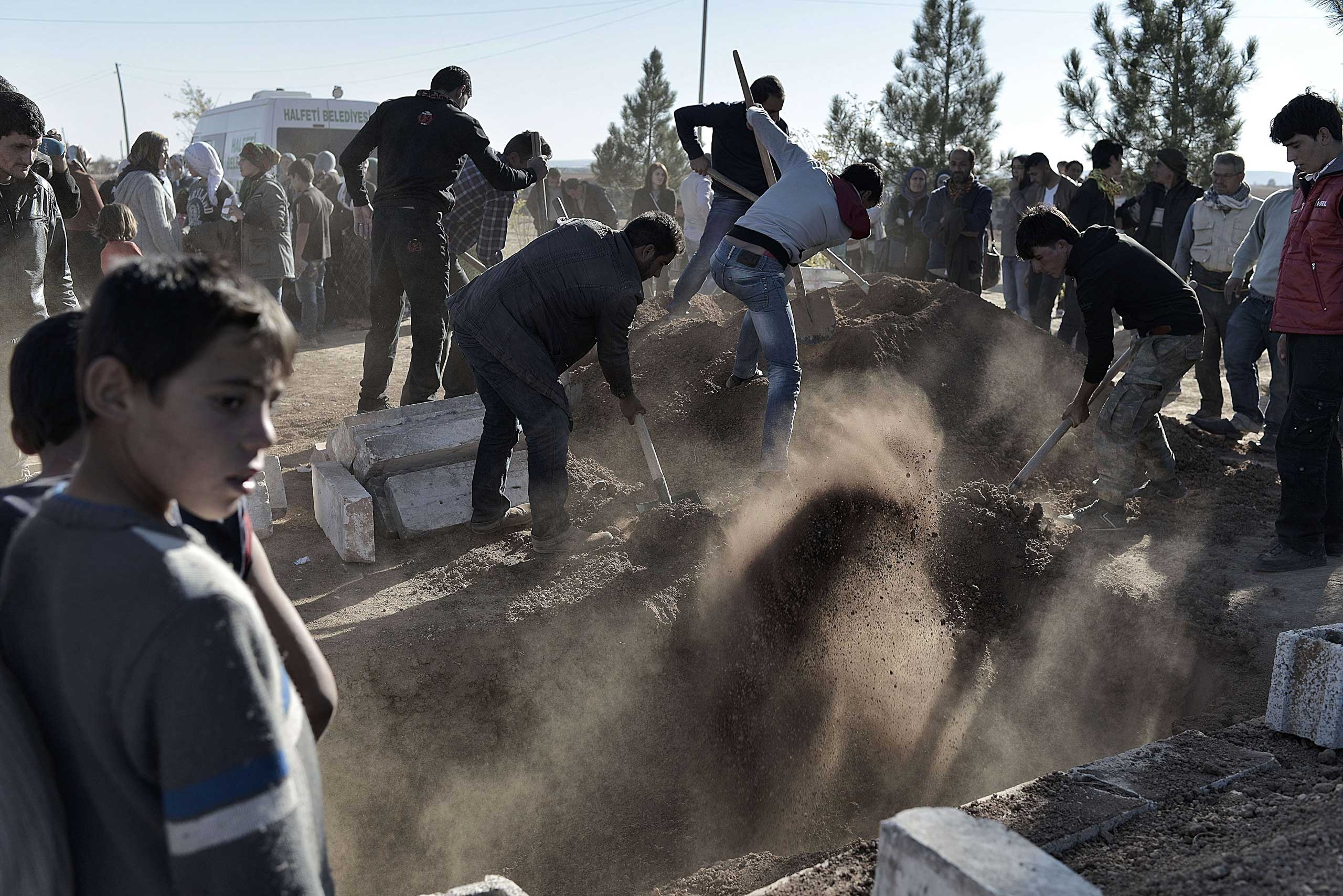 Nov. 6, 2014.                                Kurdish men bury the coffin during the funeral of a Kurdish People's Protection Units (YPG) fighter in Suruc, Turkish southeastern Sanliurfa province.