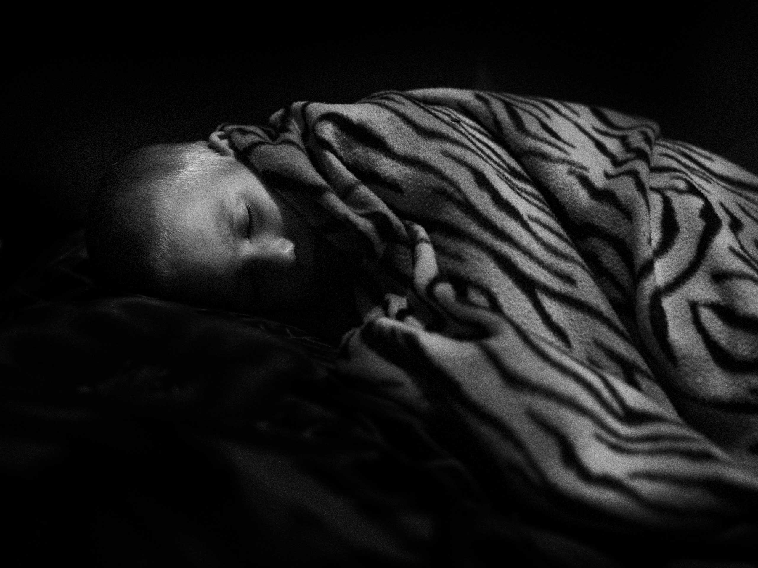 A child sleeps during the afternoon in the Trudovski shelter. Trudovski, Donetsk Oblast, Ukraine. Oct. 18, 2014.