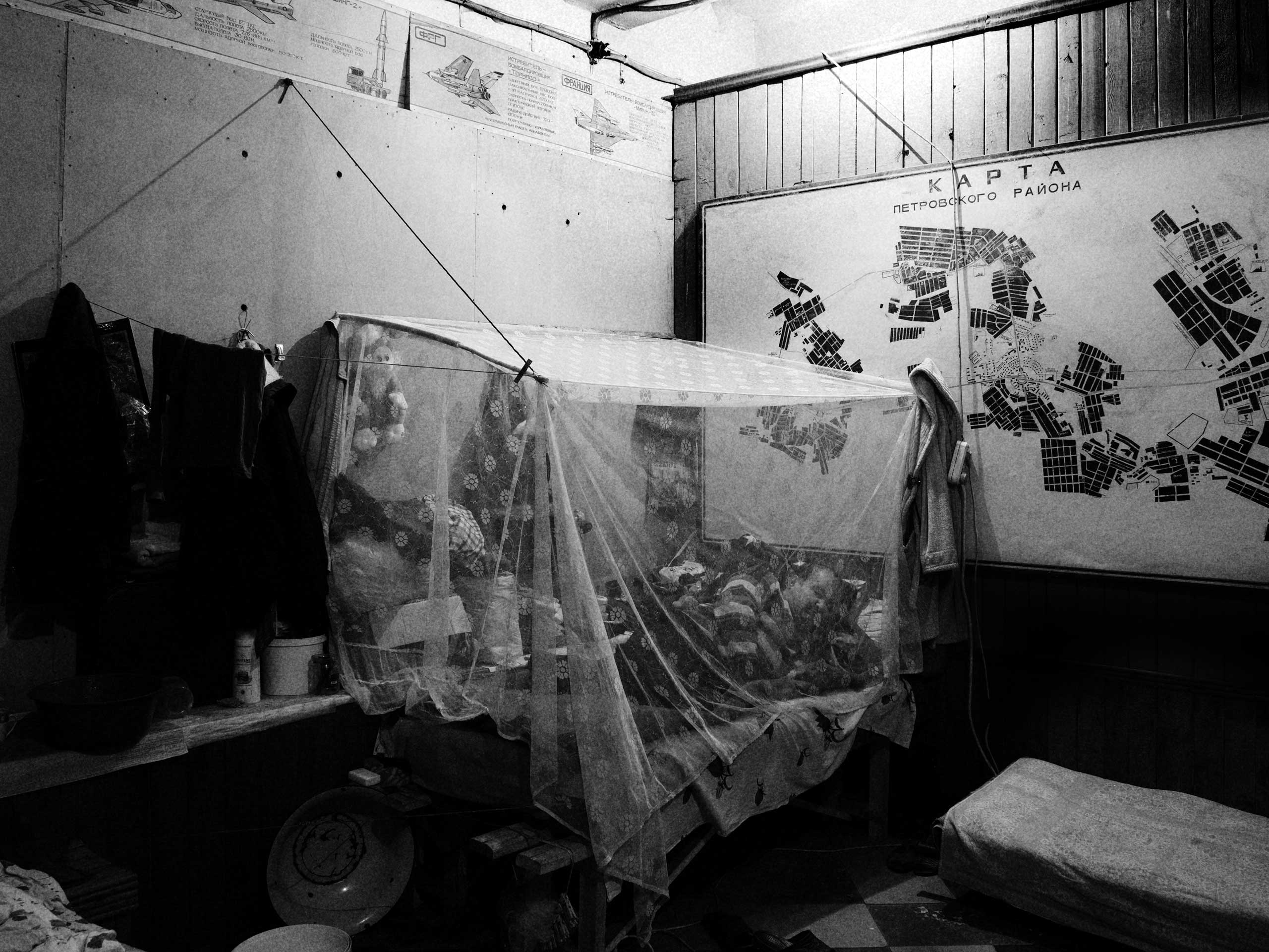 Aslanova is  deaf and mute and lives with his wife, two of their grandchildren and their dog in the shelter in Trudovski. He rests in a mosquito net under images of foreign fighter planes that signs warn are responsible for potential attacks and a map of the Trudovski region. Trudovski, Donetsk Oblast, Ukraine. Oct. 31, 2014.