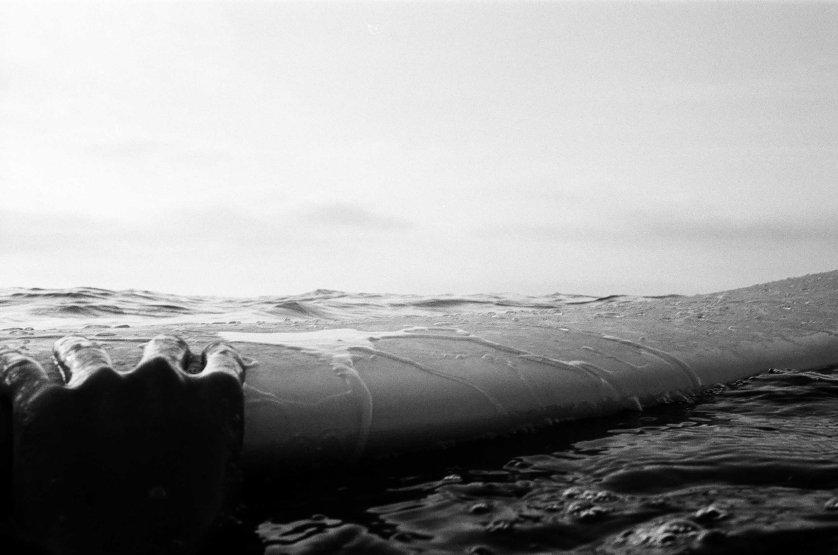 Mar Cubillos holds on to a surfboard by Rockaway beach, N.Y. in Aug. 2014