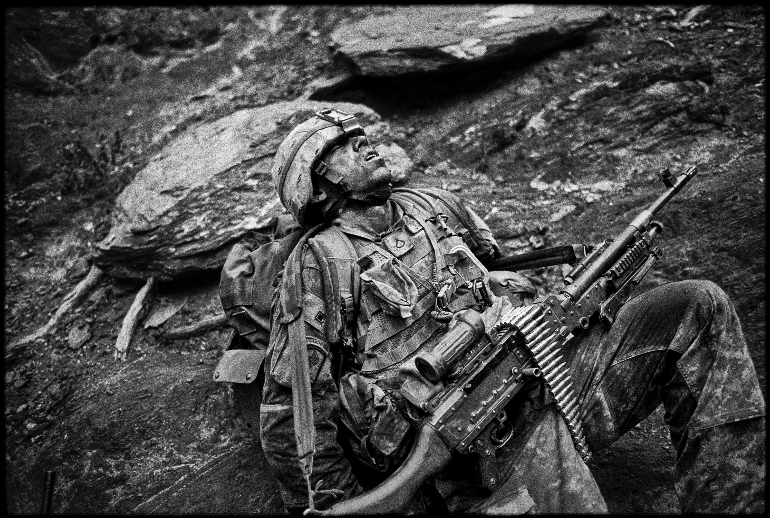 Sterling Jones.                       Balazs Gardi, Oct. 25, 2007. Korengal Valley, Afghanistan.                                                Minutes before the ambush men from Battle Company's Second Platoon stood surrounded by tall pine trees on top of the Abas-Ghar ridge listening to Specialist Sterling Jones spill a seemingly endless train of jokes, a performance that would put most professional comedians to shame. This was the third time I visited the notorious Korengal Valley, arguably the most dangerous battlefield in the Afghan war theatre at the time. This 6 miles long valley was just as crucial to smuggle in weapons and fighters from neighboring Pakistan almost three decades ago to crush the Soviet army as it was in 2007 to fight the occupying US forces. Seconds after the firefight broke out I saw Jones standing behind a giant tree trunk unleashing a shower of lead towards the invisible enemy. While we were pinned down the insurgents overran the nearby position of the scouts unit killing Staff Sergeant Larry Rougle.At the time I took this photo of Jones towards the end of the operation I did not know that same night his Company would lose two more soldiers, Sergeant Josh Brennan and Specialist Hugo Mendoza, nor that the US Army would abandon its posts in the Korengal Valley only a few years later.                                              When I look at this image I not only see an exhausted paratrooper but the faces of the comrades he lost, the bodies of dead villagers and the wounded women and children he saw. The photo of Jones makes me think of the true achievements and the real cost of war.