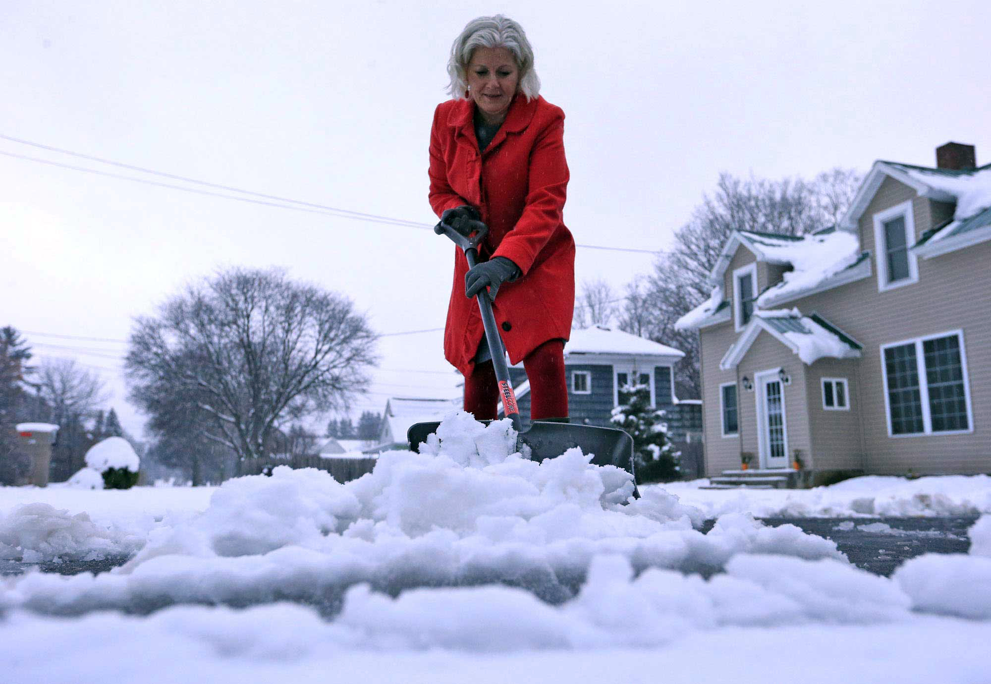 Lynette Johnson moves snow in front of her Mill Street home in Springville, NY on Nov. 17, 2014.