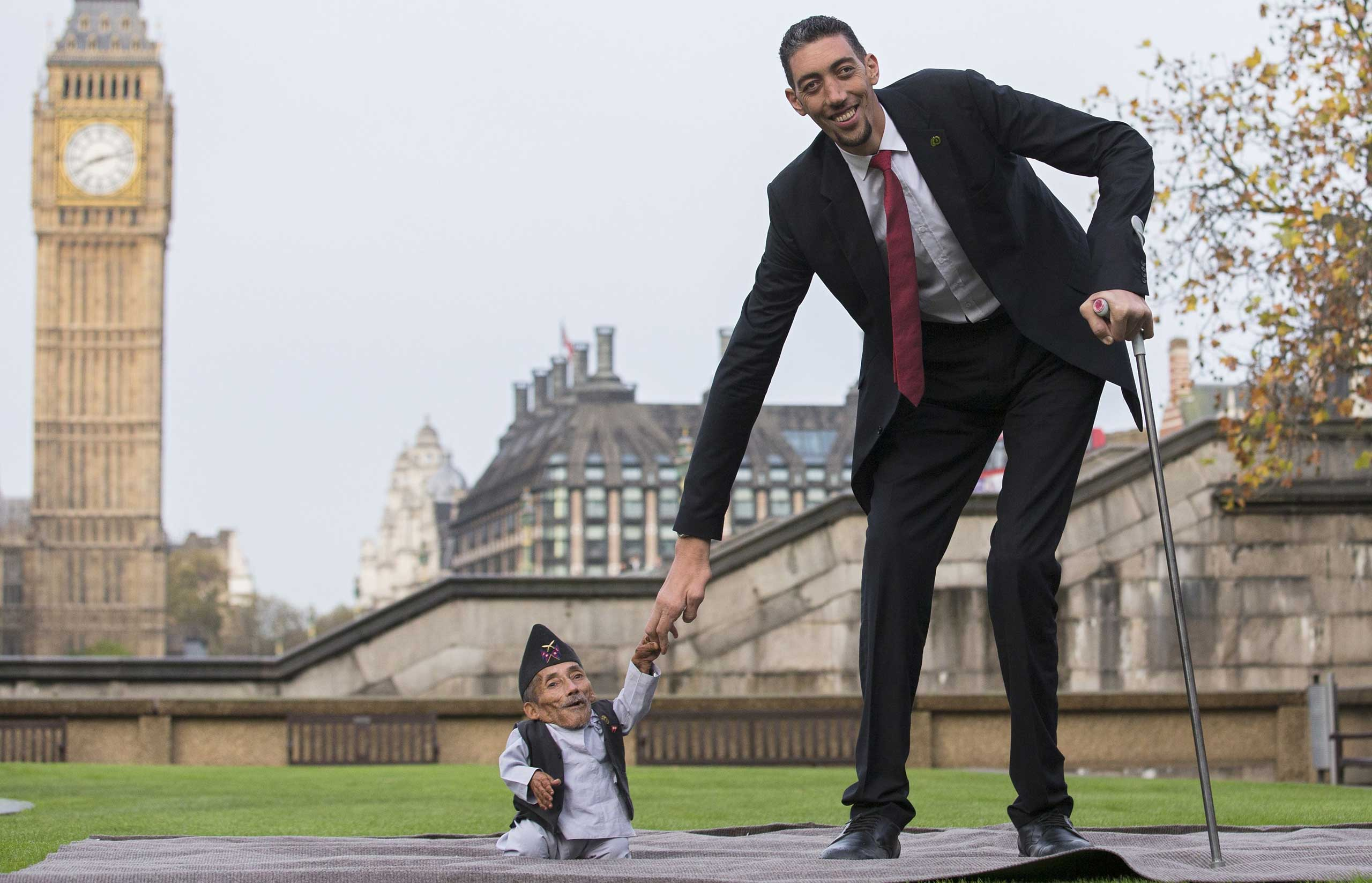 From Left: Chandra Bahadur Dangi from Nepal the shortest adult to have ever been verified by Guinness World Records poses for pictures with the world's tallest man Sultan Kosen from Turkey during a photocall in London on Nov. 13, 2014.