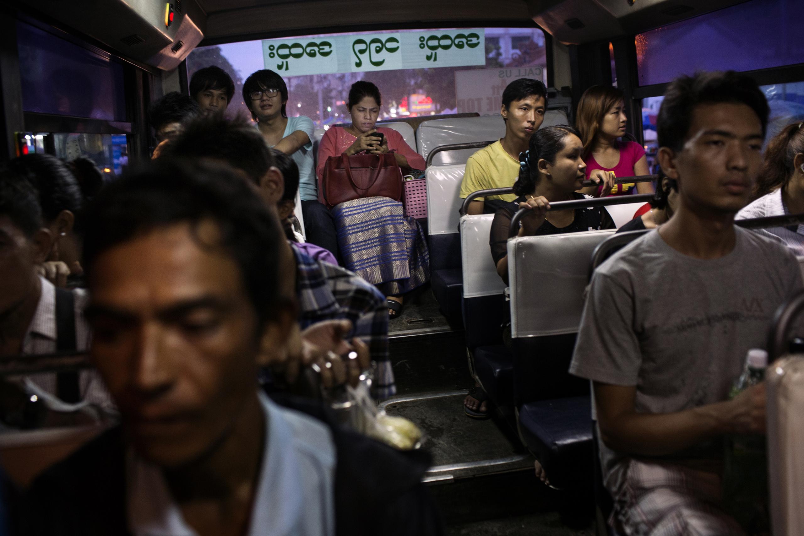 Passengers, some using smart phones, ride a bus in Yangon, Burma, June 21, 2014.