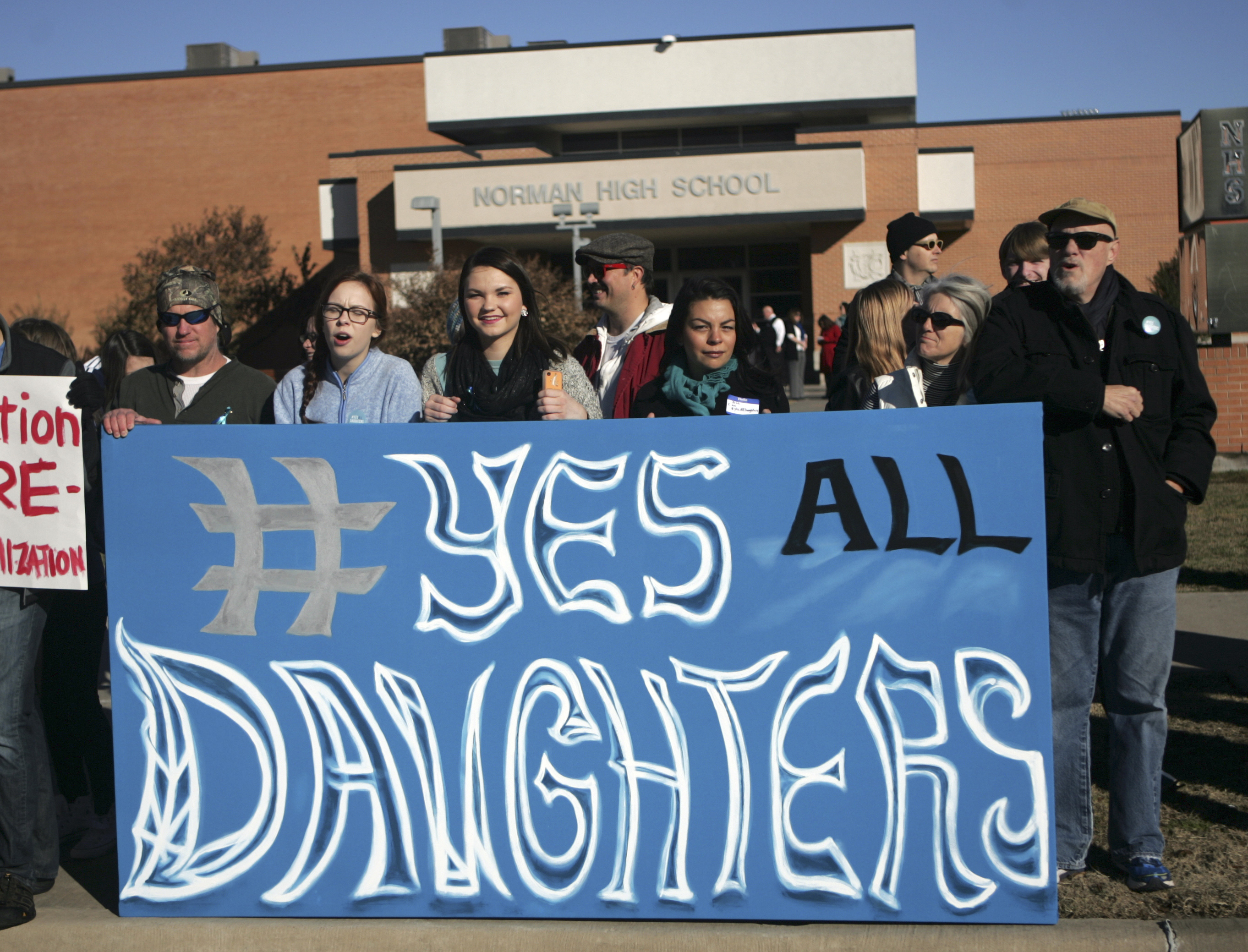Students and parents holds up a sign during protest outside Norman High School, Monday, Nov. 24, 2014, in Norman, Okla.