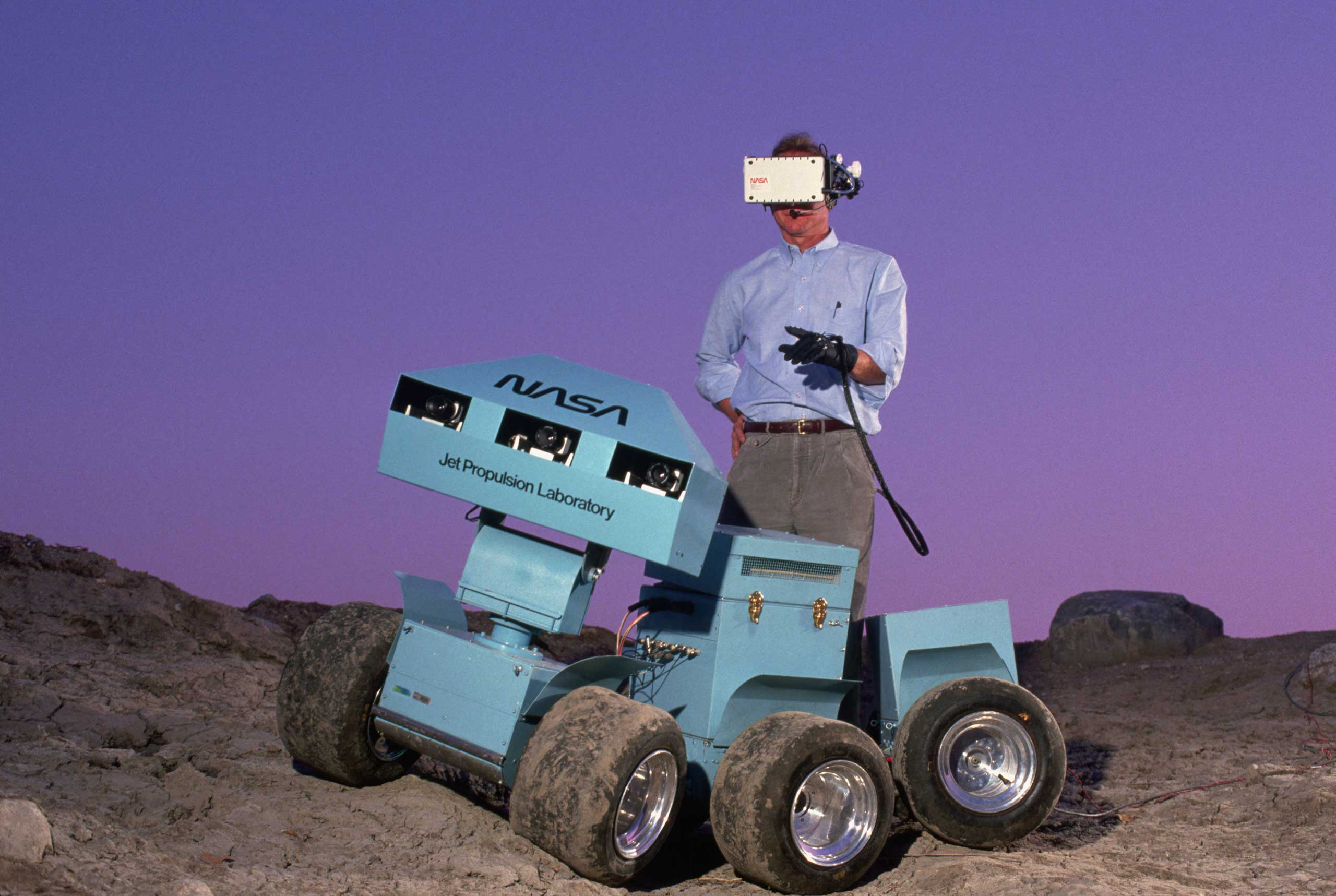1988                                                              Andrew Mishkin wearing a 3-D virtual display helmet that is connected to a six-wheeled roving vehicle. The rover was meant to explore the surface of Mars and send back information.