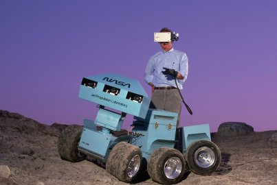 Andrew Mishkin wearing a 3-D virtual display helmet that is connected to a six-wheeled roving vehicle. The rover was meant to explore the surface of Mars and send back information.