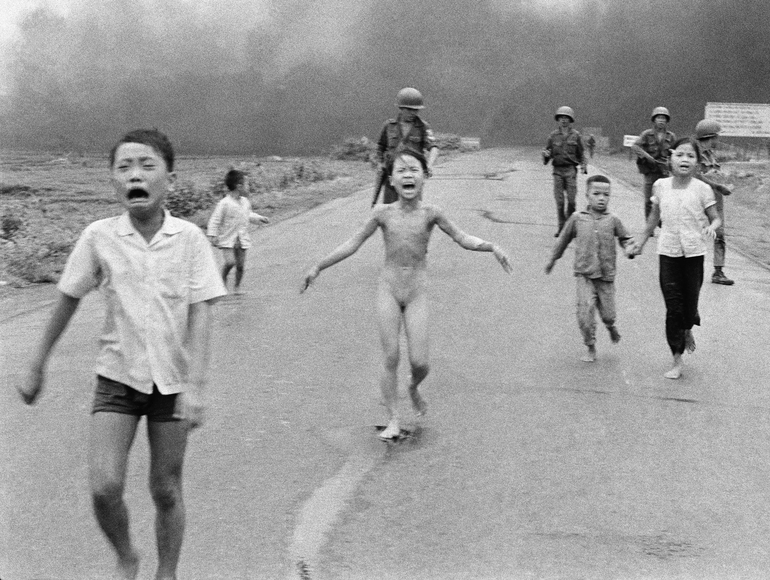 South Vietnamese forces follow after terrified children, including 9-year-old Kim Phuc, center, as they run down Route 1 near Trang Bang after an aerial napalm attack on suspected Viet Cong hiding places on June 8, 1972.