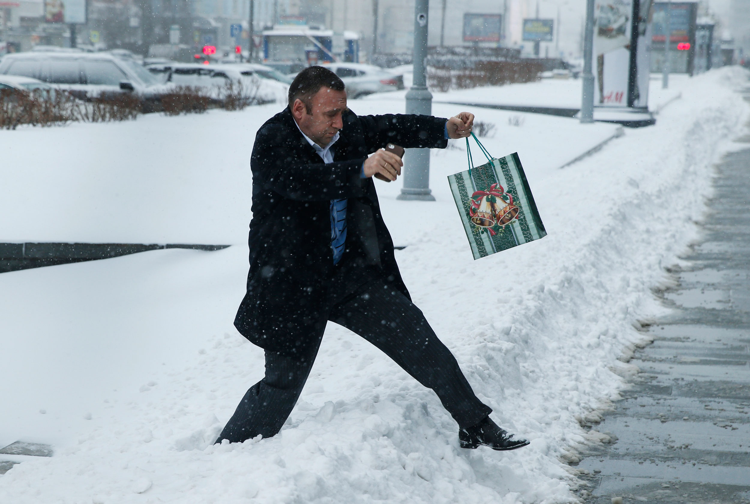 A man with a Christmas gift walks across snow during heavy snowfall in downtown Moscow on Dec. 25, 2014.