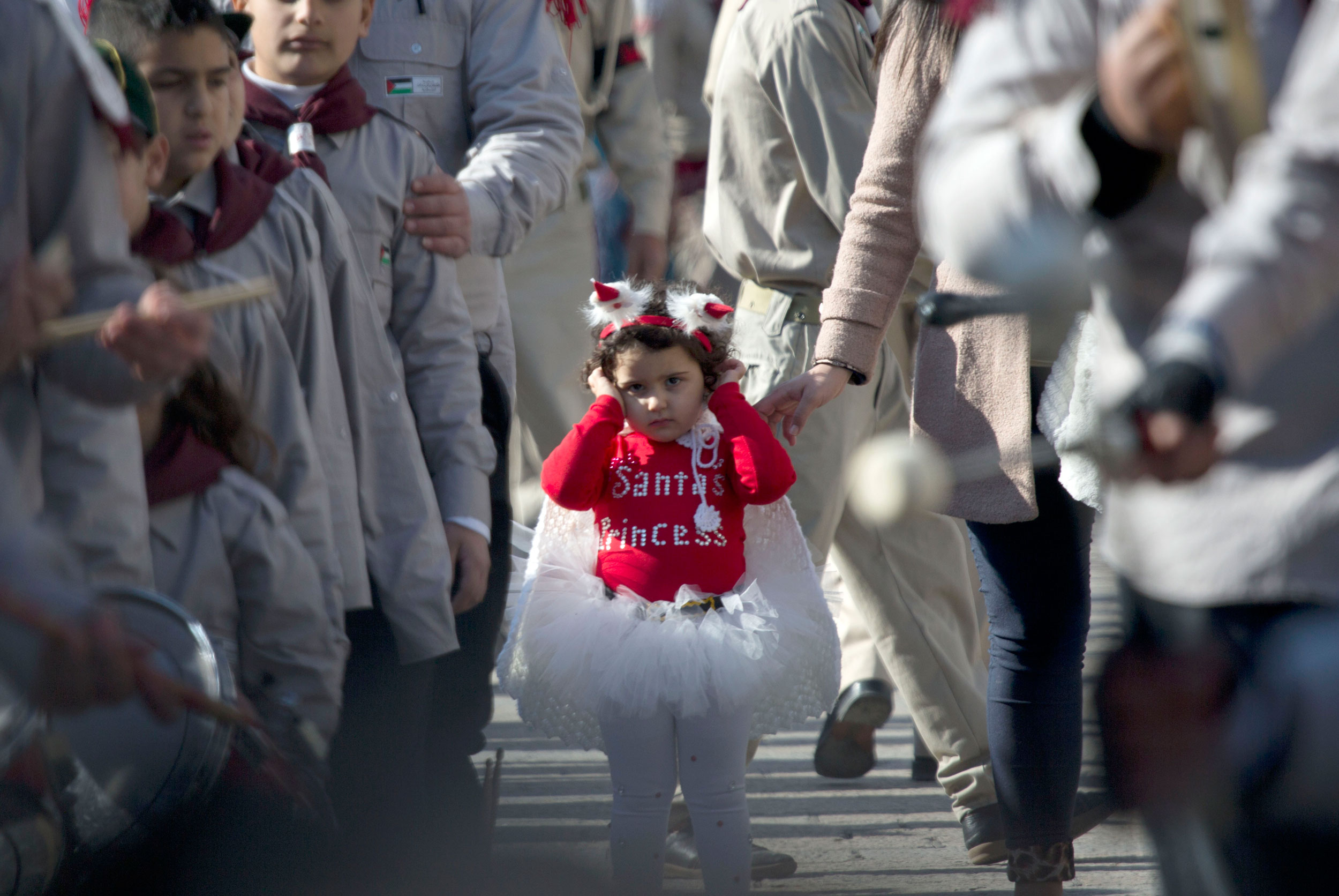 A Palestinian girl dressed in a costume joins a Christmas Eve celebration at Manger Square outside the Church of the Nativity, built atop the site where Christians believe Jesus was born, in the West Bank town of Bethlehem on Dec. 24, 2014.