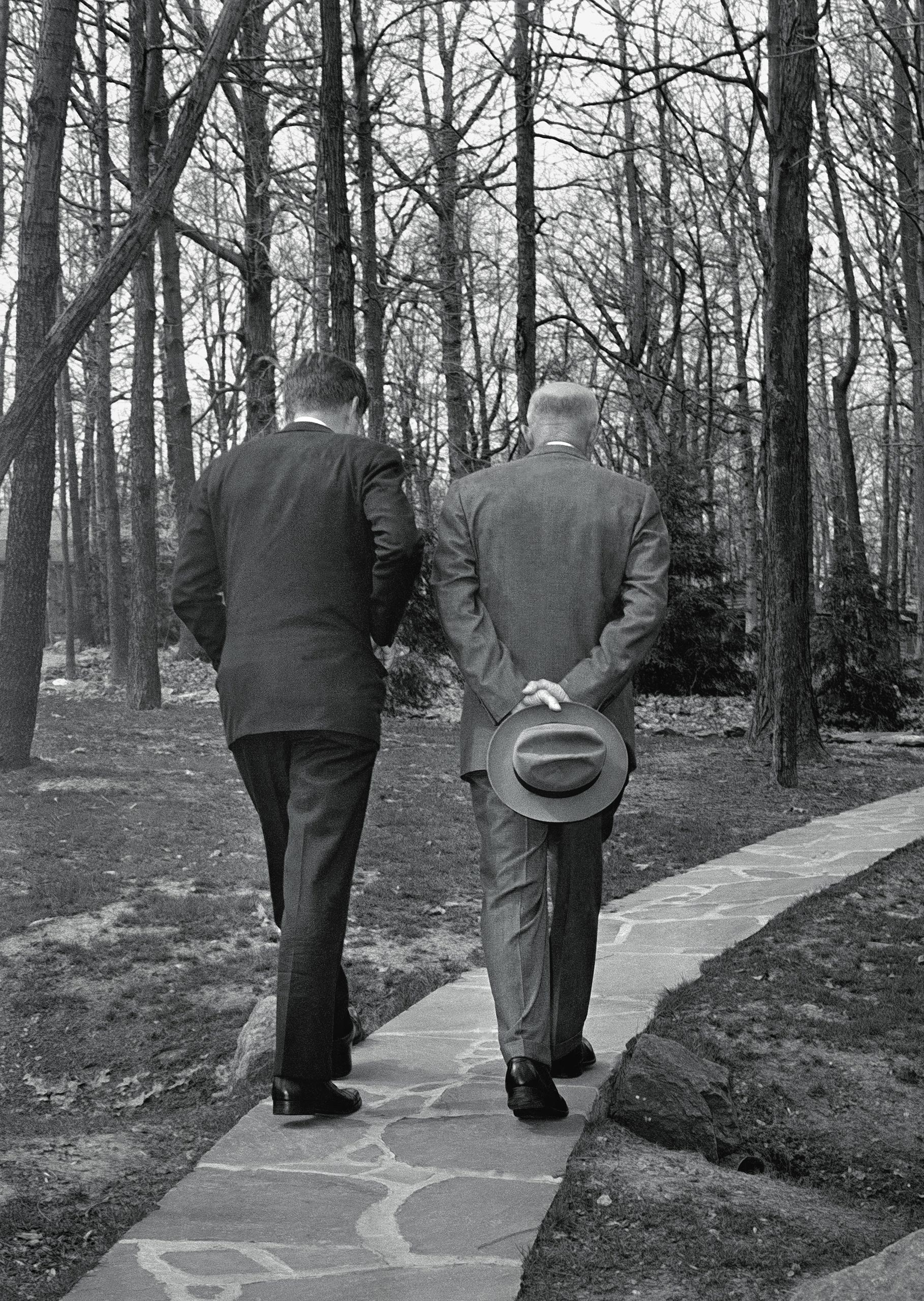 With their heads bowed, President John F. Kennedy, left, walks along a path at Camp David near Thurmont, Md., with former President Dwight D. Eisenhower on April 22, 1961, as the two met to discuss the Bay of Pigs invasion.