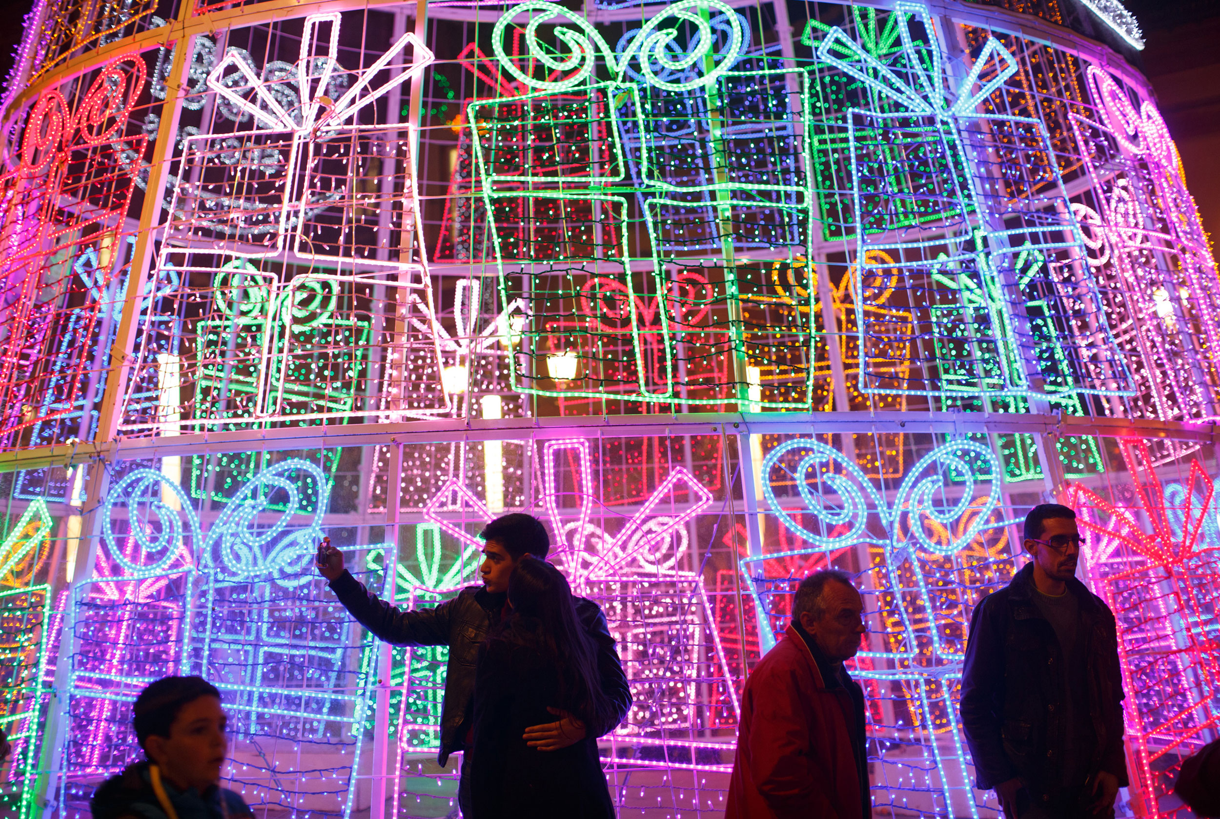 A couple poses for a  selfie  next to a light installation for Christmas celebrations in the Andalusian capital of Seville, southern Spain on Dec. 23, 2014.
