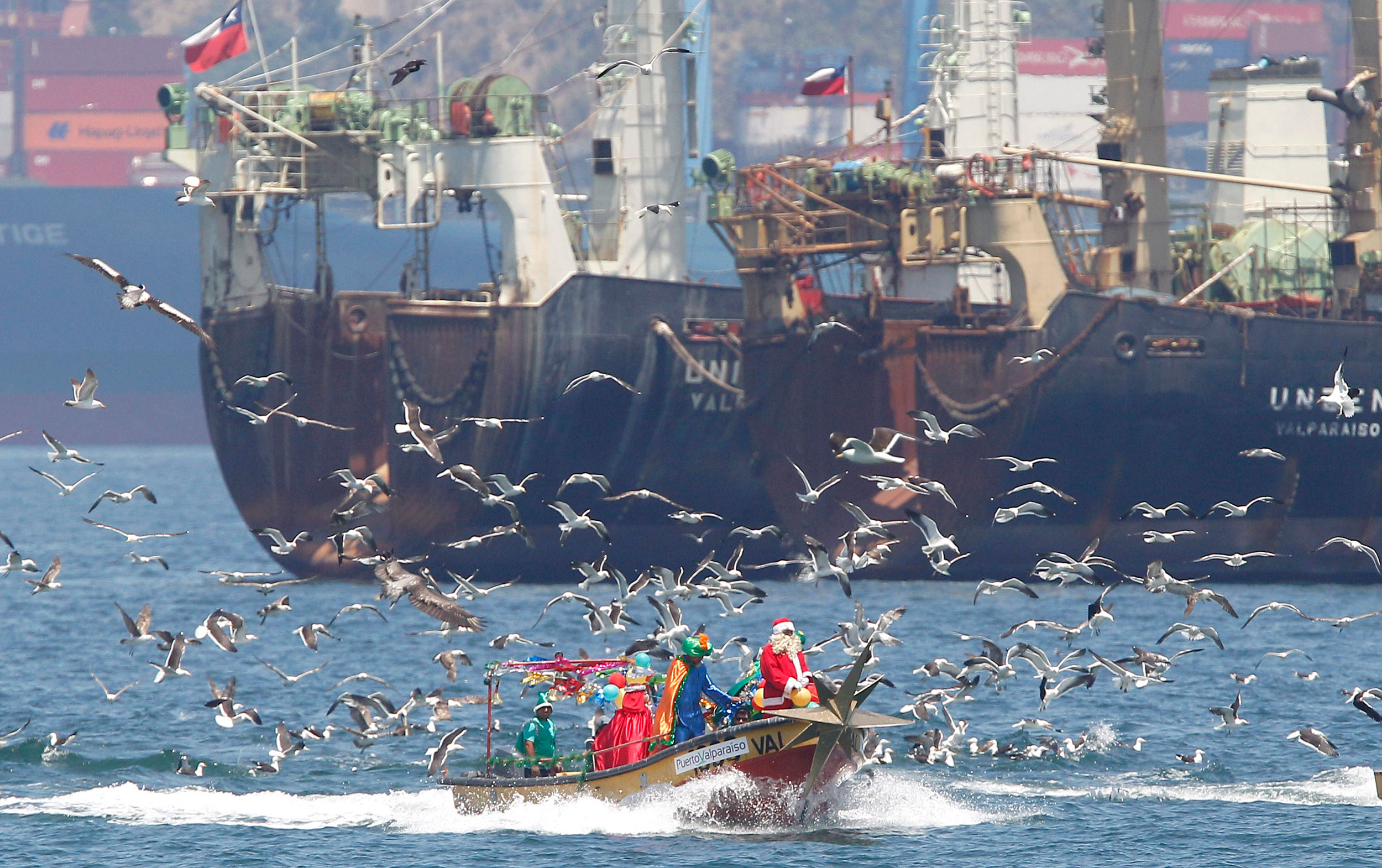 Ruben Torres, dressed in a Santa Claus outfit, and fishermen stand on a boat on Christmas Eve along the coast of Valparaiso city, northwest of Santiago on Dec. 24, 2014. Every year, the fishermen organize a Santa Claus boat trip as people wait on the shore to receive their Christmas presents and well-wishes.