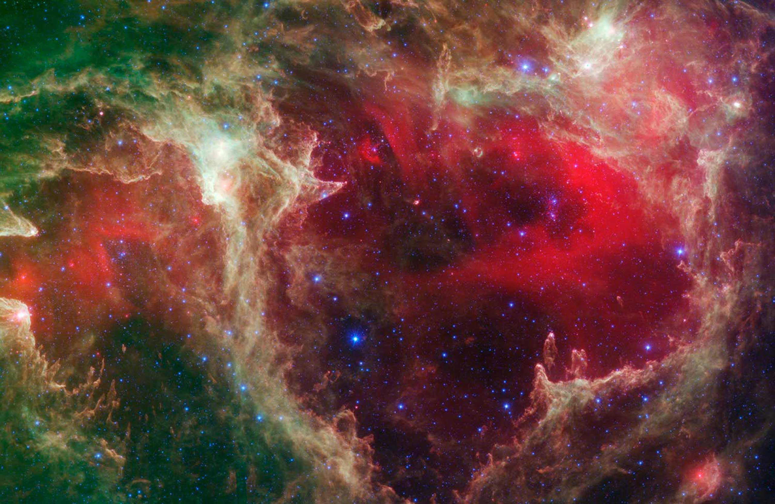 Generations of stars, seen in an infrared portrait from NASA's Spitzer Space Telescope, in the star-forming region, W5. The oldest stars can be seen as blue dots. Younger stars line the rims of the cavities where the old ones are nestled, and some can be seen as pink dots at the tips of the elephant-trunk-like pillars. The white knotty areas are where the youngest stars are forming. Red shows heated dust, while green indicates dense clouds.