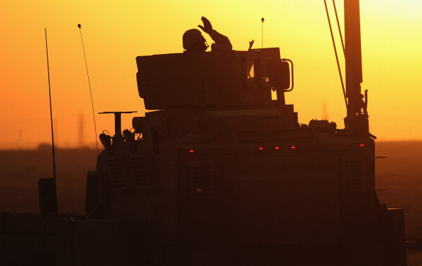 A U.S. soldier waves as the final American convoy pulls out of Iraq in 2011 at the end of the second Iraq war.