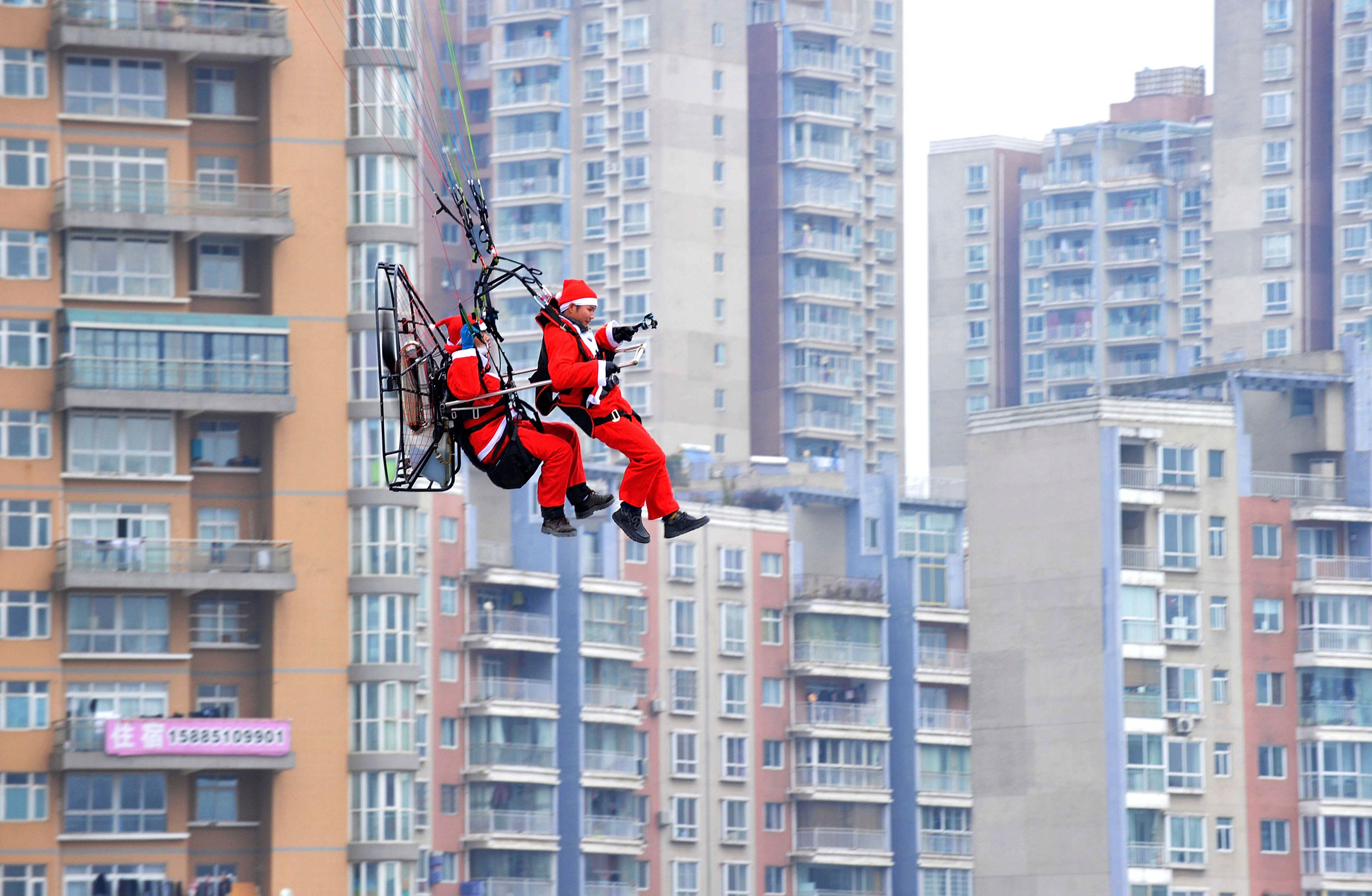 Members of a local parachute club wearing Santa Claus costumes fly past residential buildings to drop presents to pedestrians during a promotional event celebrating Christmas in Guiyang, Guizhou province on Dec. 24, 2014.