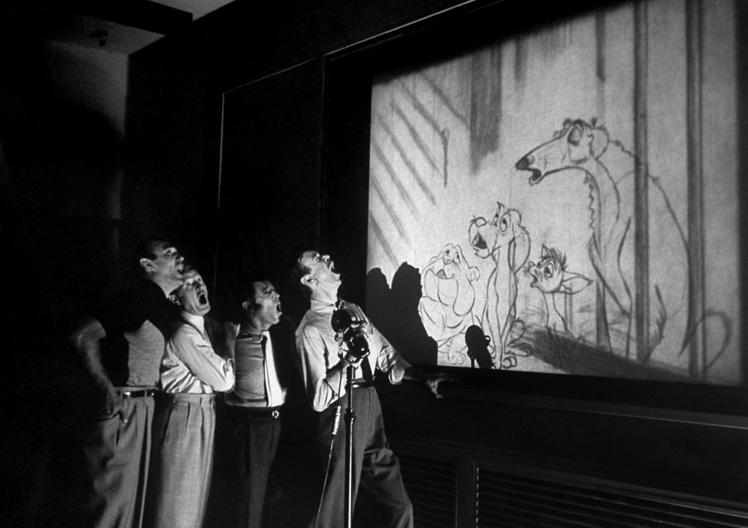 Caption from LIFE. Quartet known as The Mello-Men bays in harmony before screen showing four canine characters whose voices they represent in the forthcoming Disney feature cartoon,  The Lady and The Tramp.