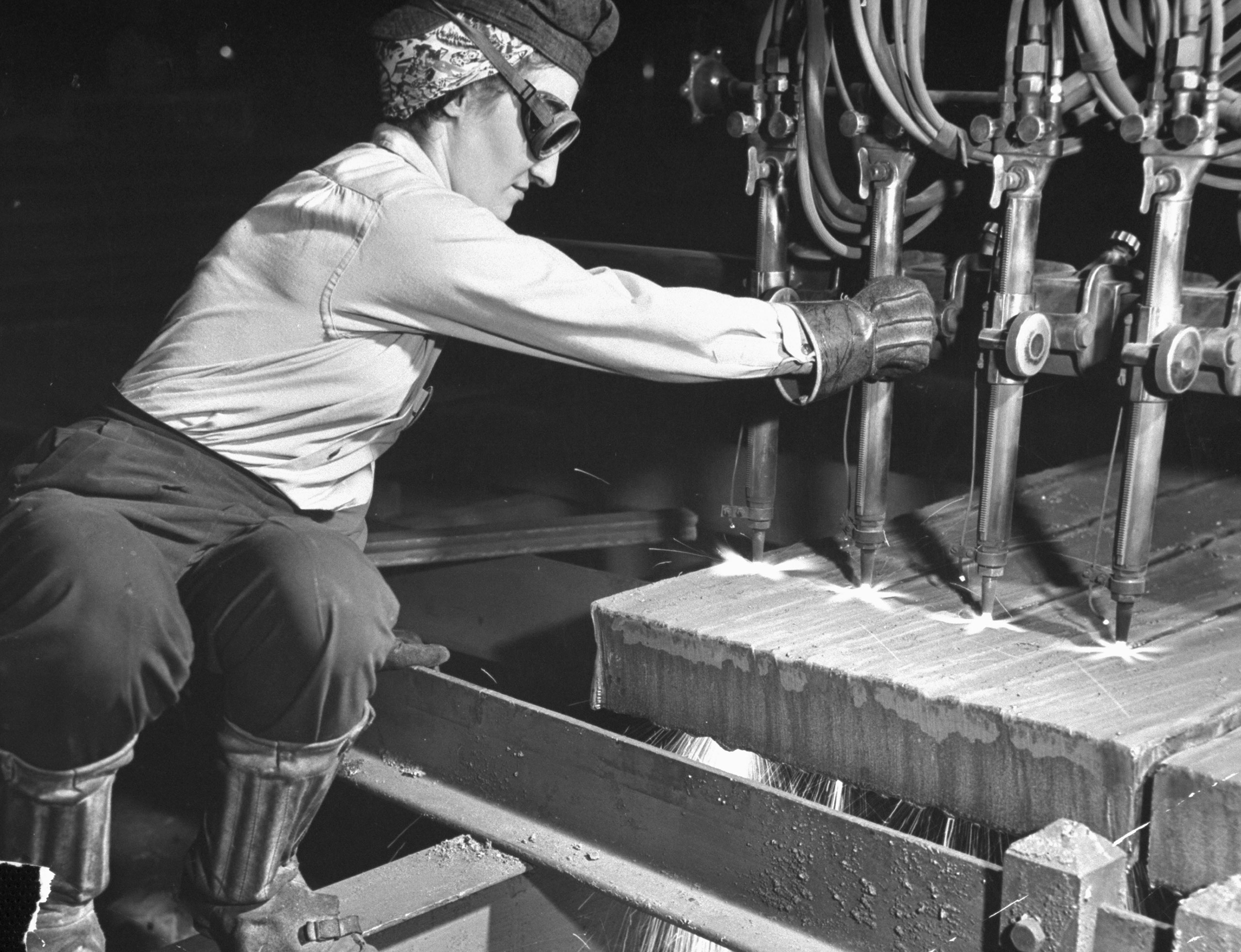 <b>Caption from LIFE.</b> Flame cutting of a slab is done by four-torch machine controlled and operated by one woman. Alice Jo Barker (above) has a husband and son who also work in war industries.