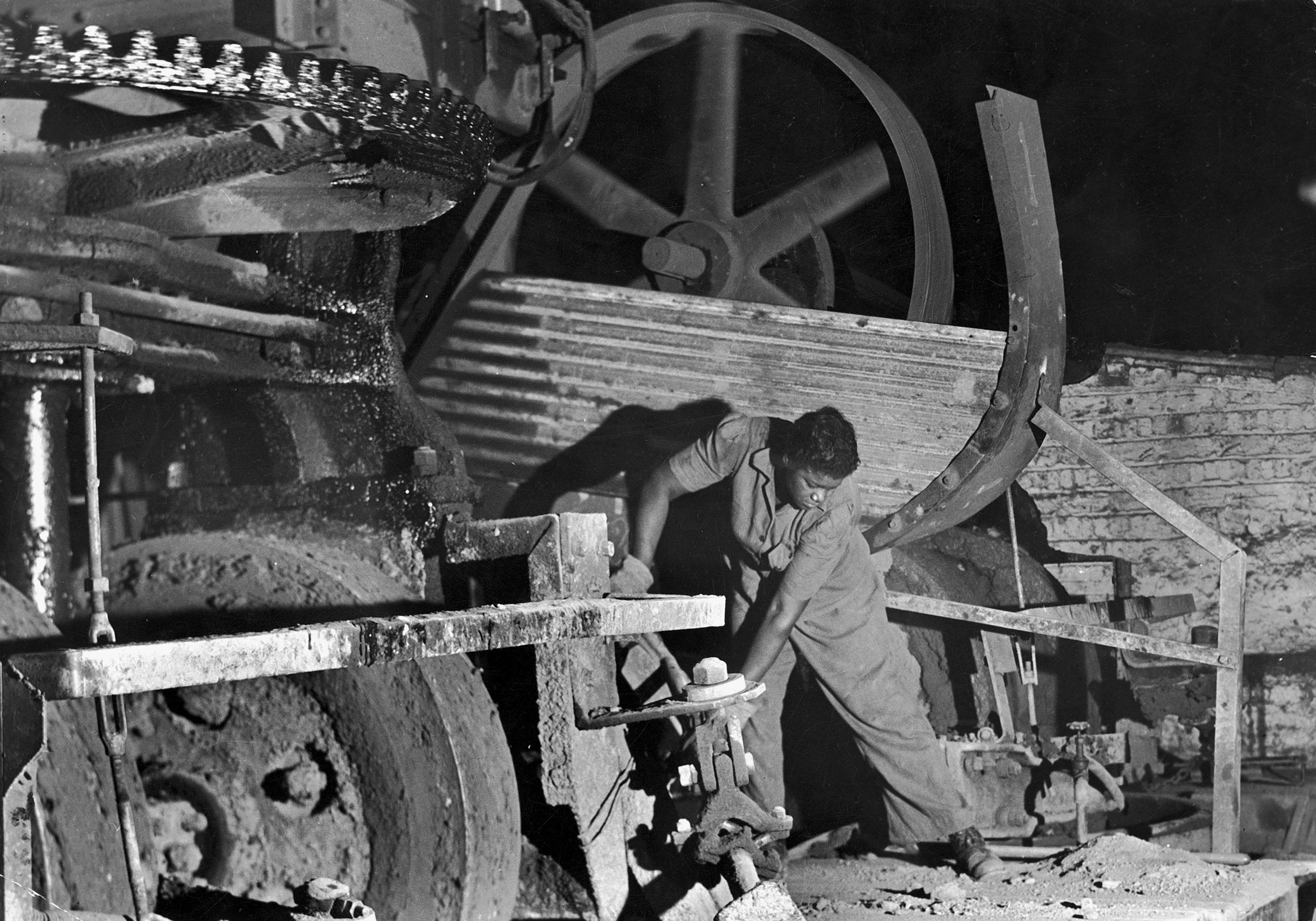 <b>Caption from LIFE.</b> Pan Man' at Gary Works is Mrs. Rosalie Ivy, a husky Negro laborer. She is mixing a special mud used to seal the casting hole through which molten iron flows from a blast furnace.