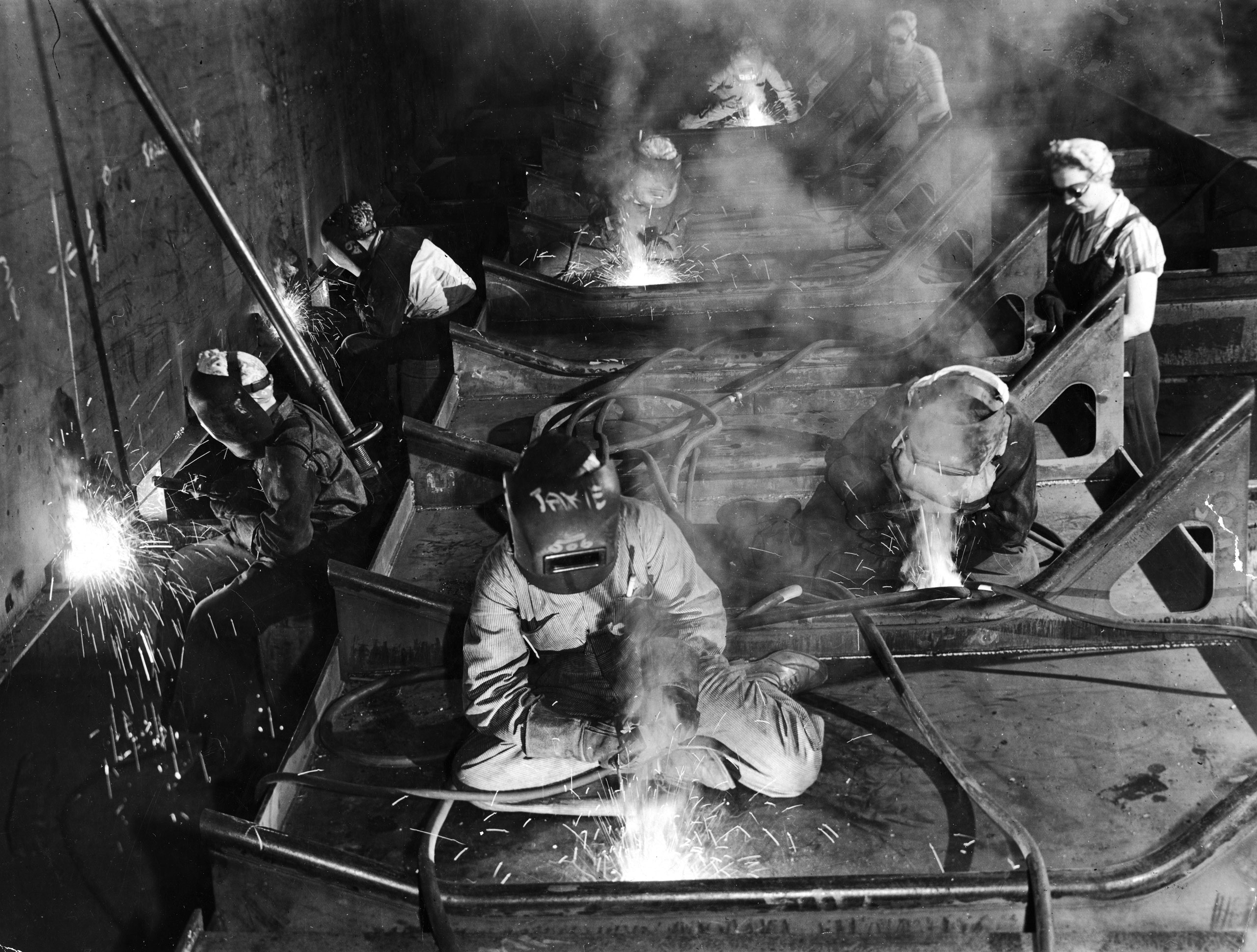 <b>Caption from LIFE.</b> On aircraft carrier deck women work as welders and scrapers. Girls alongside this steel prefabricated deck section who are without headgear and masks operate tools which scrape loose surface imperfections in preparation for welding. The welder in foreground has her name, 'Jakie,' written on helmet, a popular style note among lady welders.
