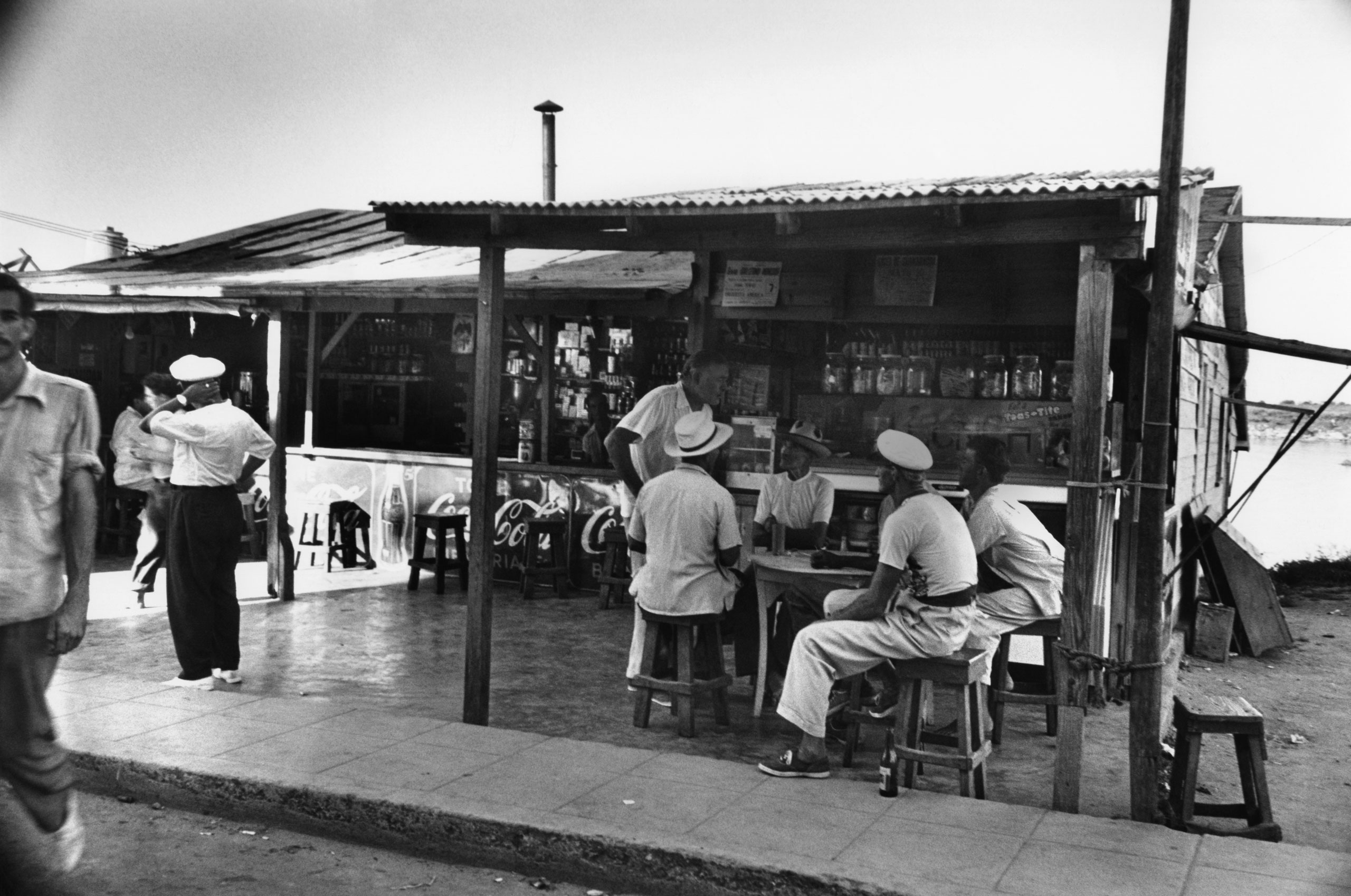 Ernest Hemingway chats with fellow patrons at a cafe he enjoyed frequenting in Cuba, 1952.