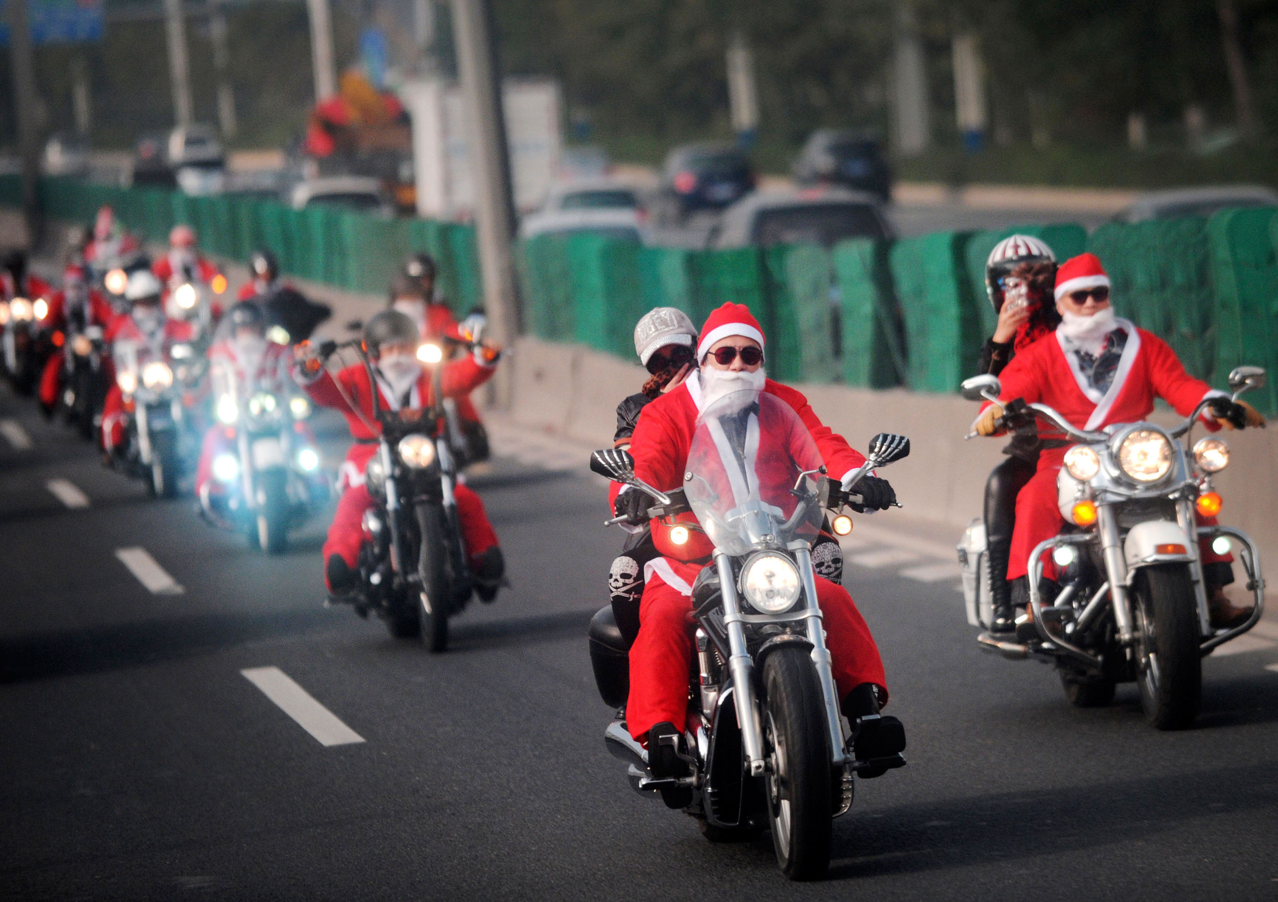 Owners of Harley-Davidson motorcycles wearing Santa Claus costumes ride along a street to give presents to elders at a nursing home during a promotional event celebrating Christmas in Guangzhou, Guangdong province on  Dec. 24, 2014.