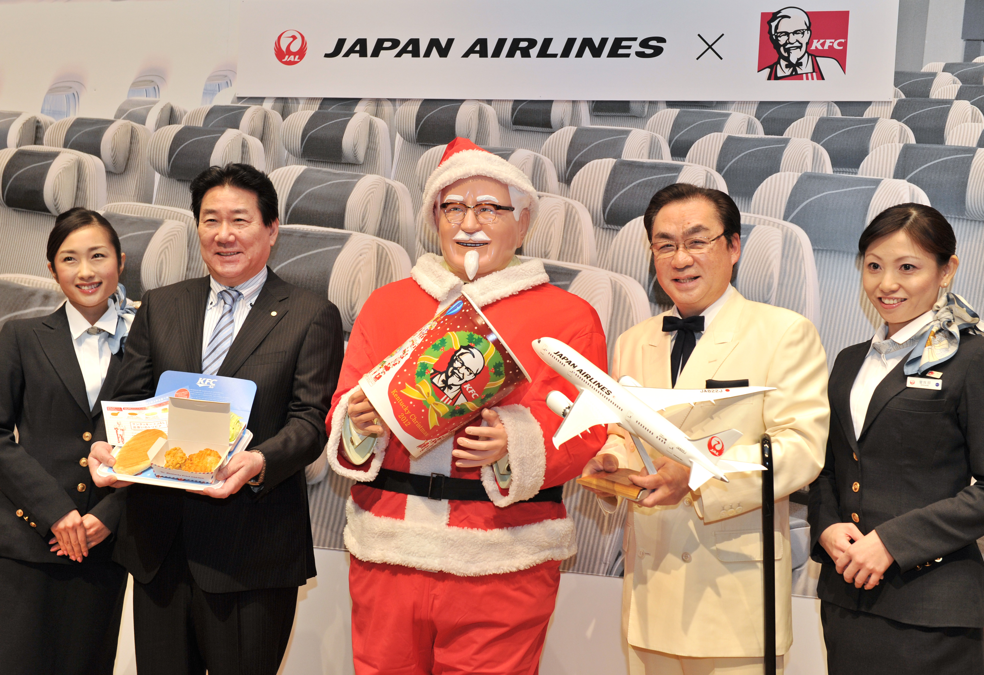 Japan Airlines President Yoshiharu Ueki (2nd L) and Masao Watanabe (2nd R), President of Kentucky Fried Chicken Japan pose with a statue of Colonel Sanders (C) wearing a Santa Claus costume during a photo session after a press conference to announce their new  AIR Kentucky Fried Chicken  in-flight fried chicken service, in Tokyo on November 28, 2012.