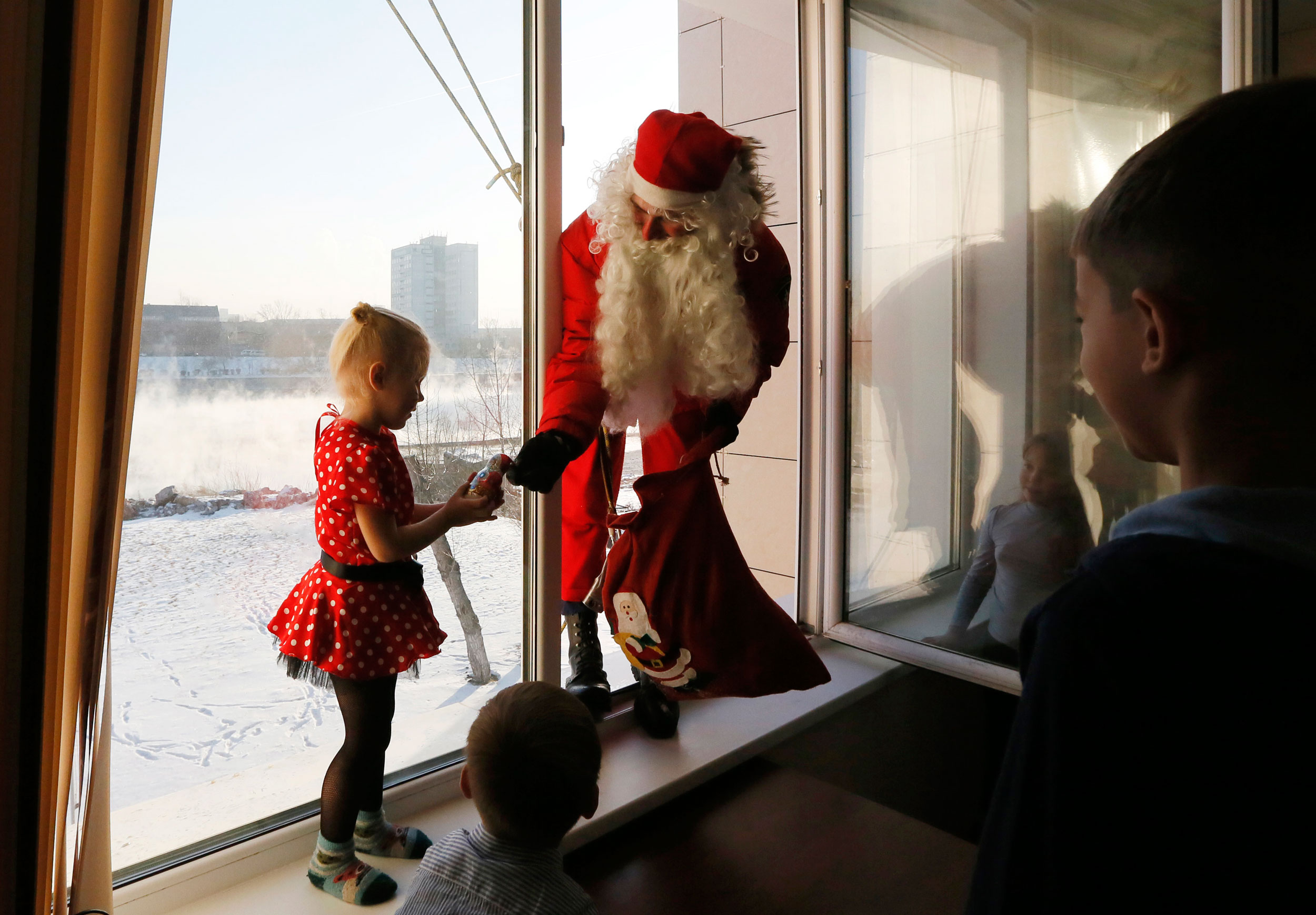 Alexei Trifonov, a member of the  rescuer  state regional service, dressed as Santa Claus, gives a sweet to a girl as he congrastulates employees of the Russian Emergencies Ministry and their children ahead of New Year and Christmas celebrations in Krasnoyarsk, Siberia on Dec. 24, 2014.