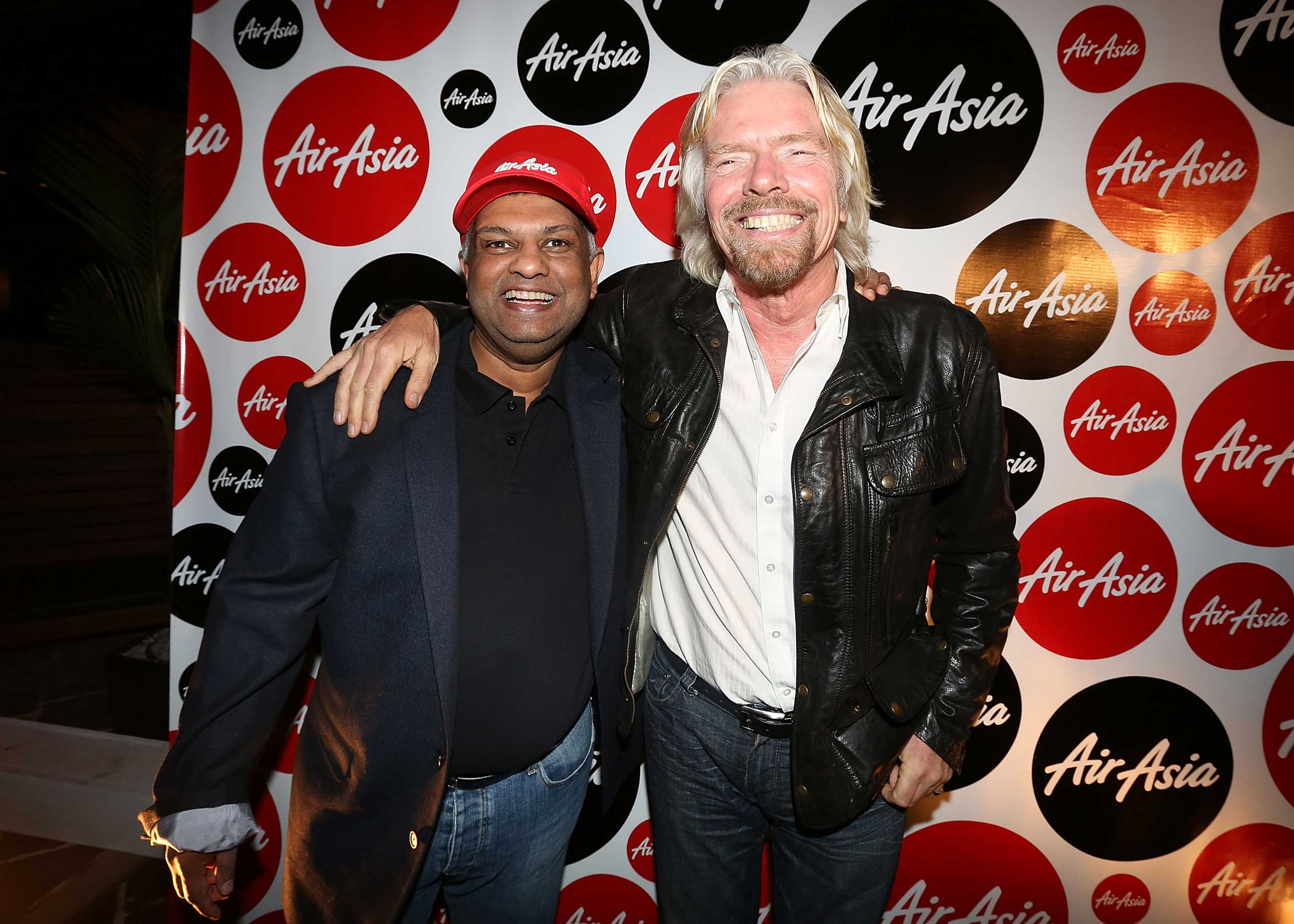 Fernandes and Sir Richard Branson at an AirAsia Cocktail Party in Perth, Australia, May 11, 2013. Fernandes' public persona has often been likened to that of Branson--and the two are in fact friends. Branson dressed as an AirAsia flight attendant after losing a bet with Fernandes on which of their 2010 Formula One racing car teams would finish ahead of the other.