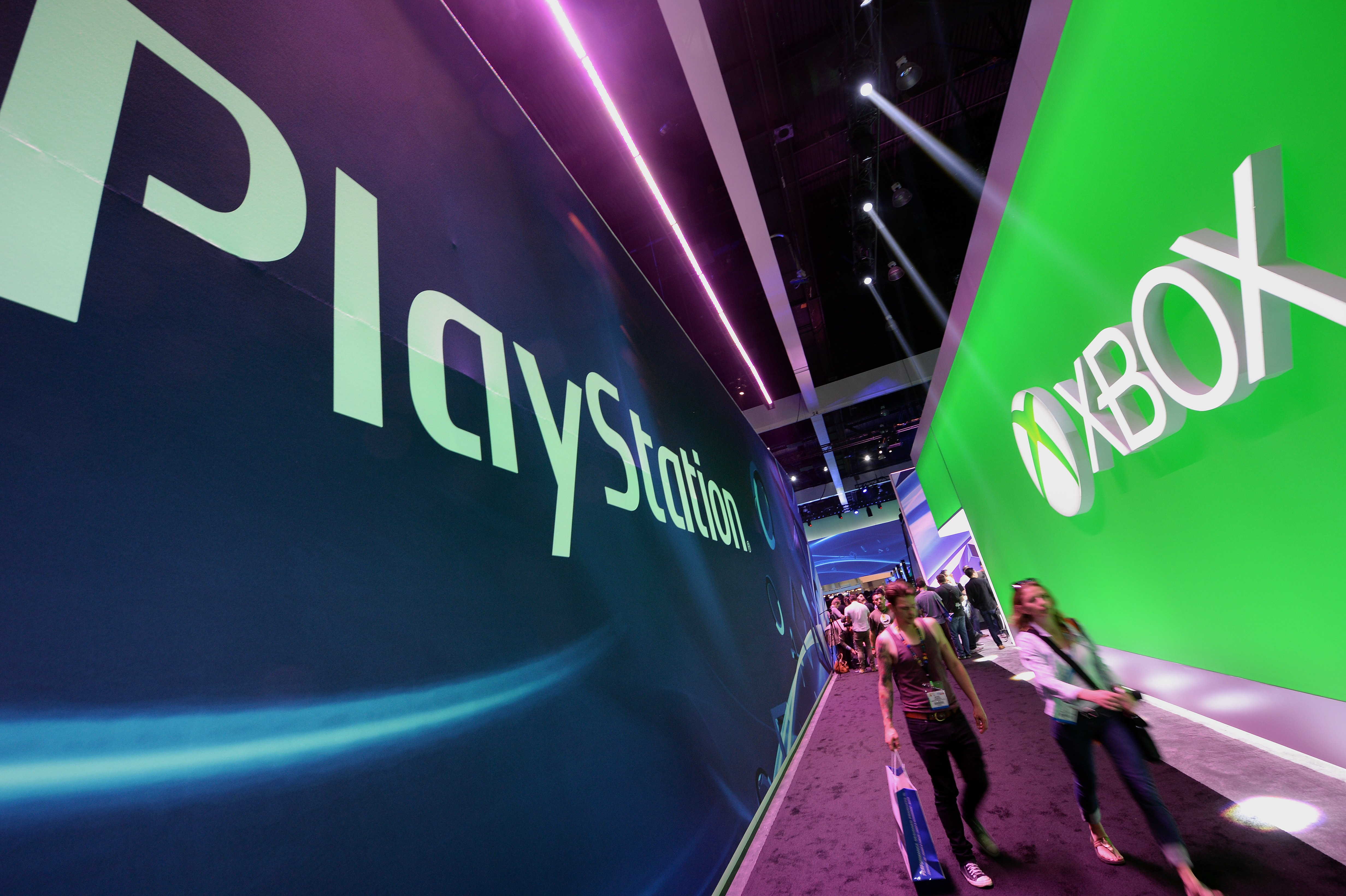 Attendees walk between signs for Sony PlayStation and Microsoft XBox on the first day of the Electronic Entertainment Expo (E3) in Los Angeles, California, June 11, 2013.