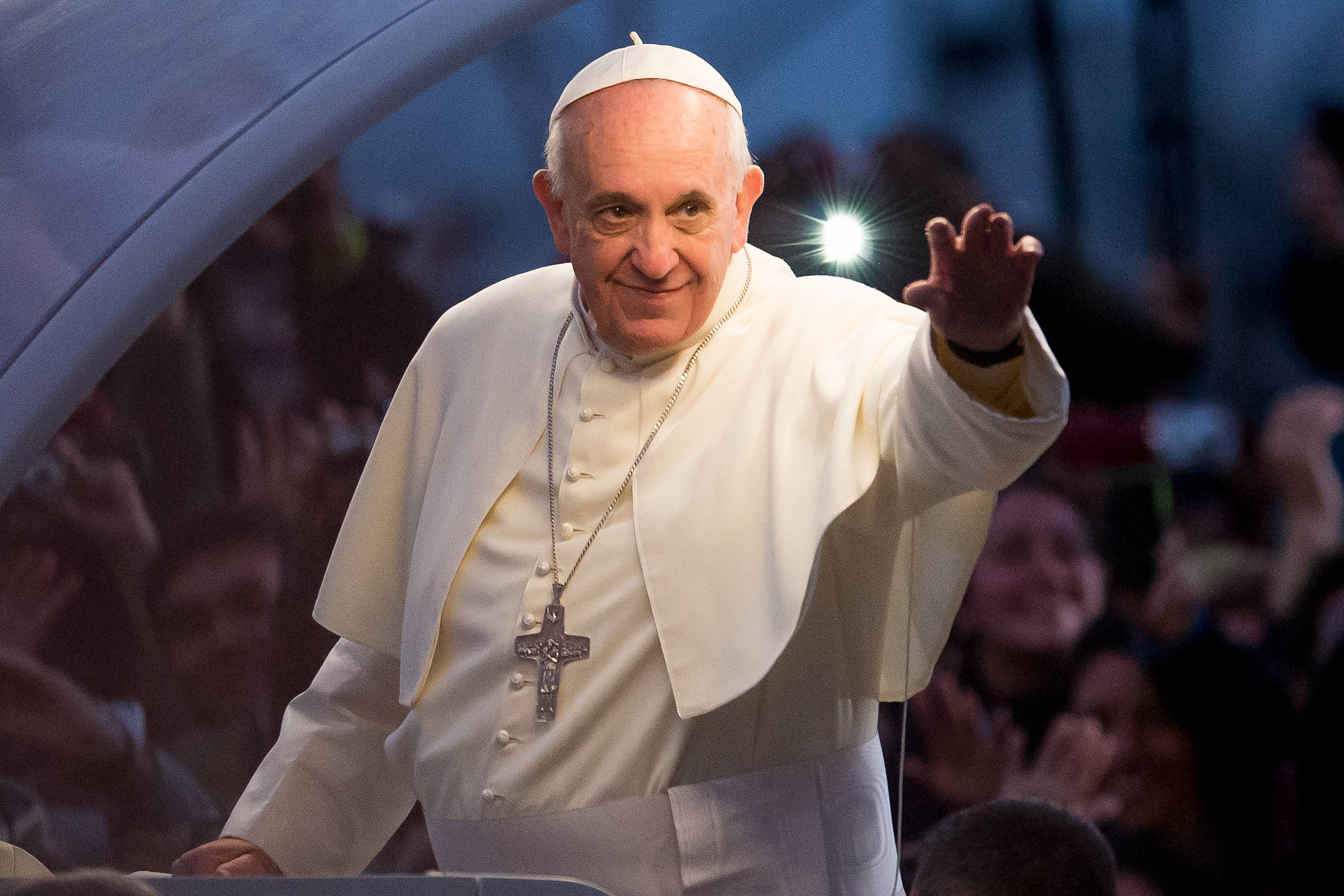Pope Francis waves from the Popemobile on his way to attend the Via Crucis on Copacabana Beach during World Youth Day celebrations in Rio de Janeiro on July 26, 2013