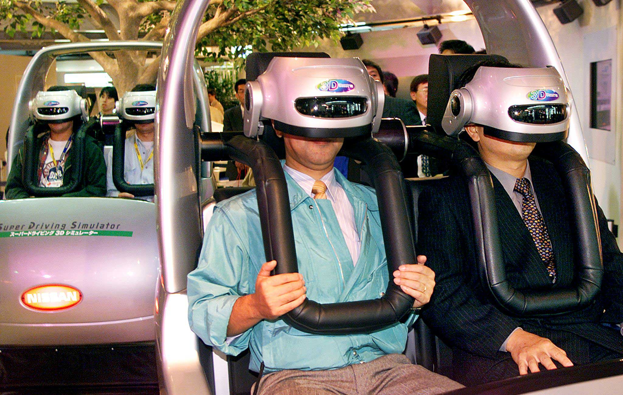 1999                                                              Visitors enjoy virtual reality driving with 3-D goggles and driving simulators for the presentation of Japan's automaker Nissan at the Tokyo Motor Show in Tokyo.