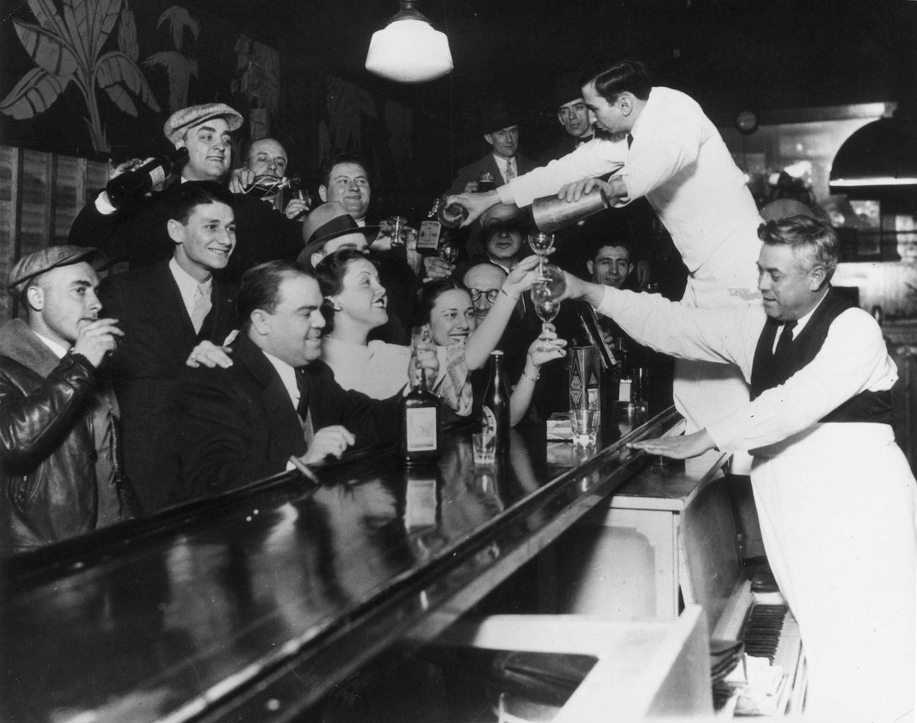 Bartenders at Sloppy Joe's in Chicago bar pour a round of drinks on the house for a large group of smiling customers as it was announced that the 18th Amendment had been repealed